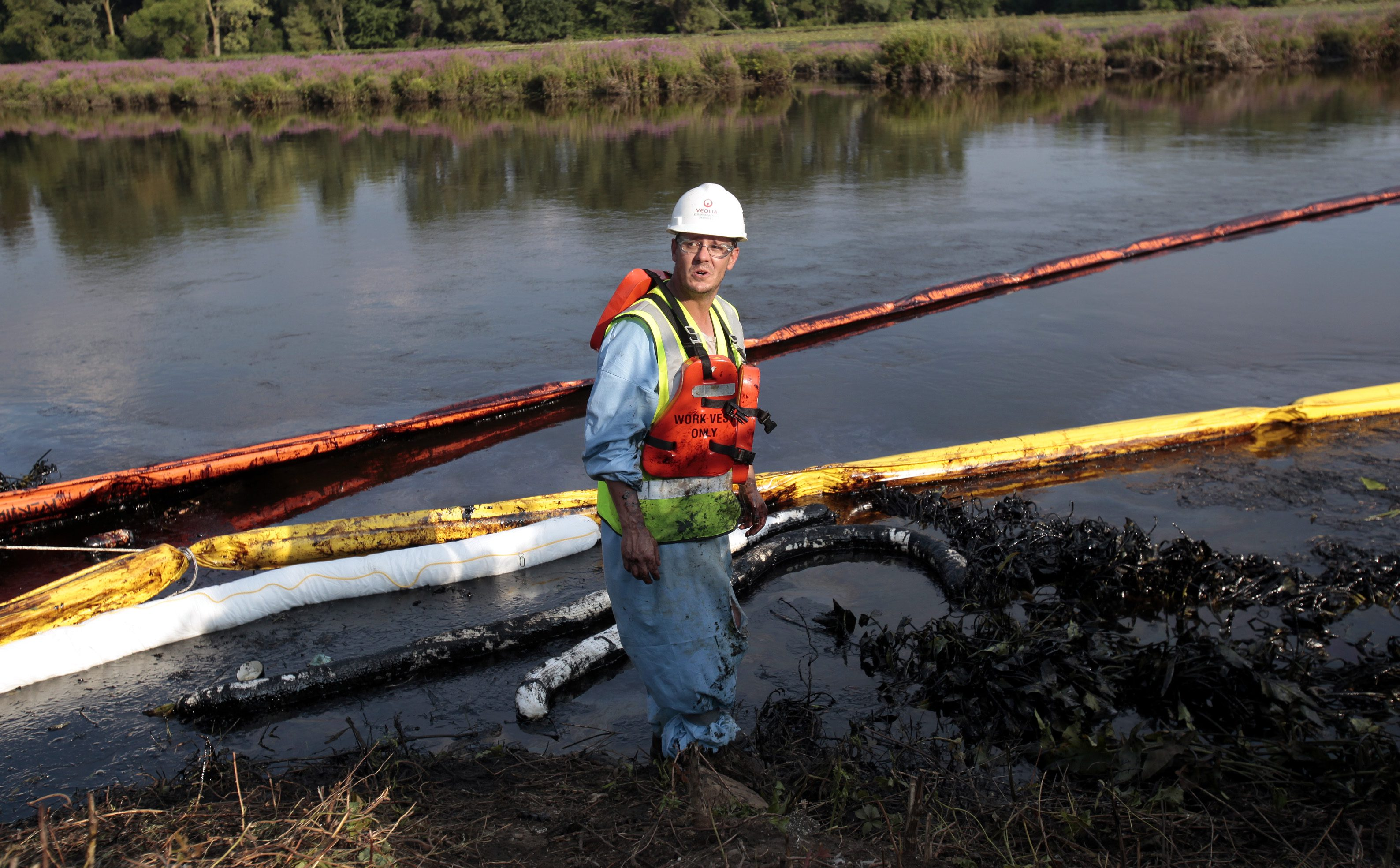 A cleanup worker places absorbent booms in the Kalamazoo river in Battle Creek after an oil pipeline, owned by Enbridge Energy Partners, leaked an estimated 820,000 gallons of oil into the river in Western Michigan near Marshall July 31, 2010.