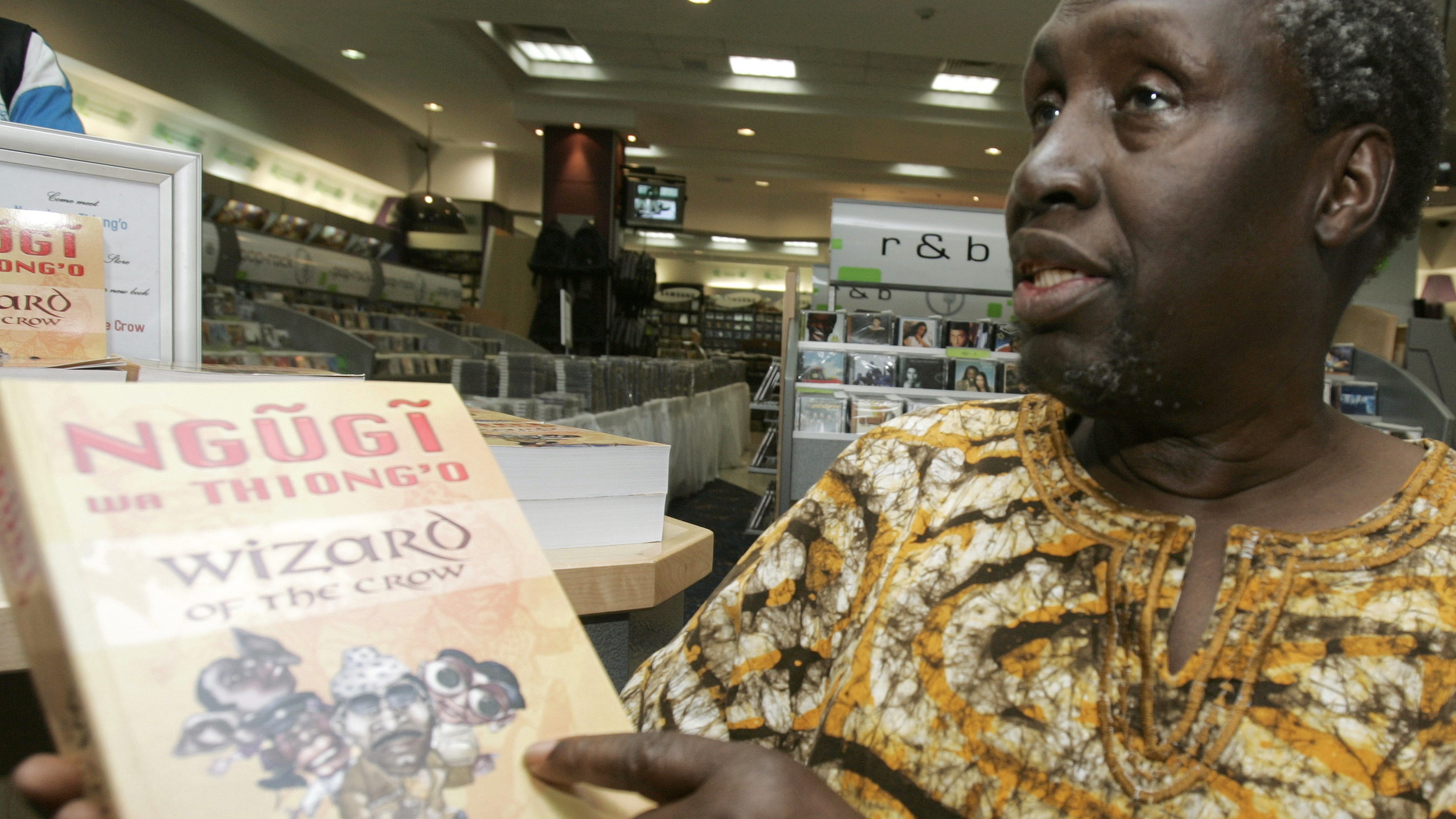 "Kenyan author Ngugi Wa Thiong'o shows his newly launched book ""Wizard of the Crow"" during an interview with Reuters at a bookshop in downtown Nairobi January 16, 2007. The book, which took Wa Thiong'o more than six years to write, was released on Monday, about 20 years after his novel ""Matigari"". REUTERS/Antony Njuguna (KENYA) - RTR1L921"