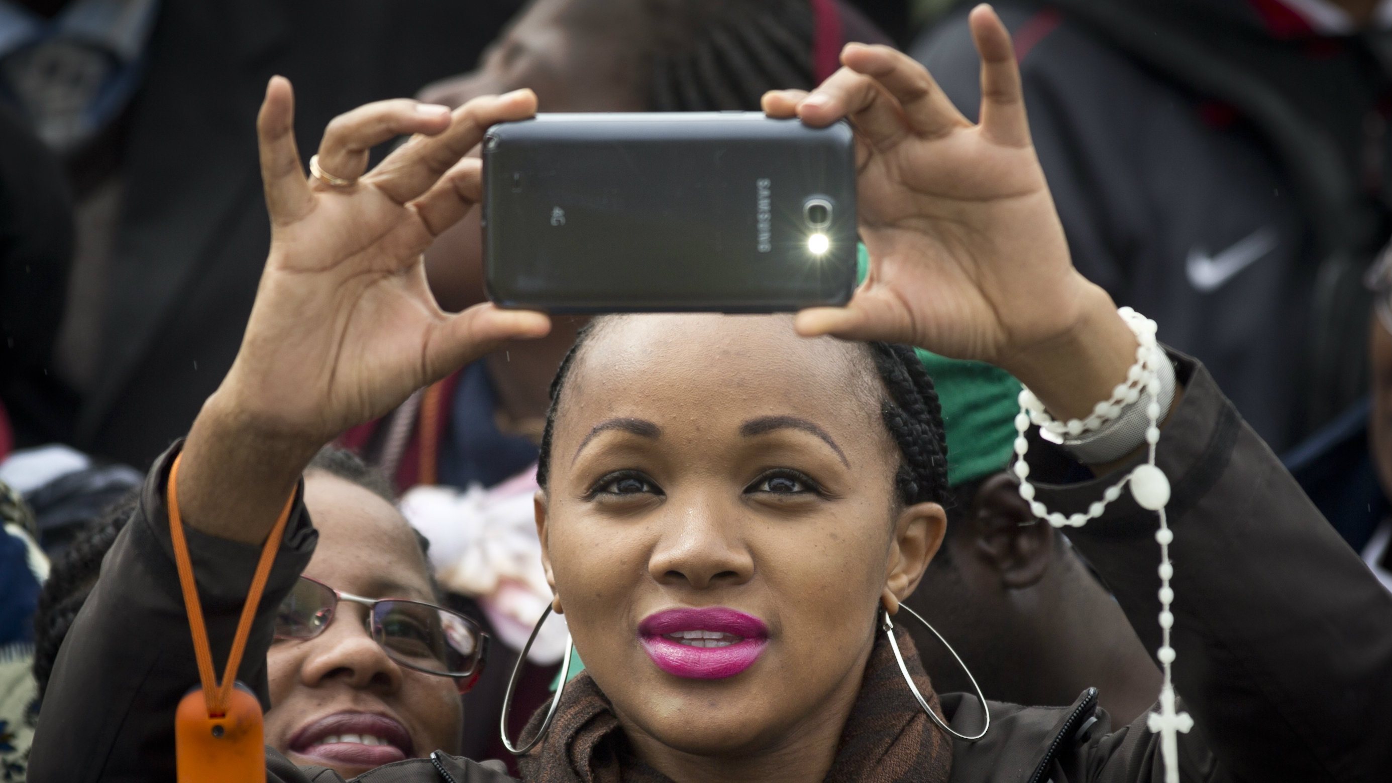 A Kenyan Catholic woman takes photographs with her smartphone as she awaits the arrival of Pope Francis to hold a Mass at the campus of the University of Nairobi in Kenya Thursday, Nov. 26, 2015. The Argentine pope, who has never been to Africa before, was treated to ululating Swahili singers, swaying nuns, Maasai tribesmen and traditional dancers at the Mass on the grounds of the University of Nairobi.