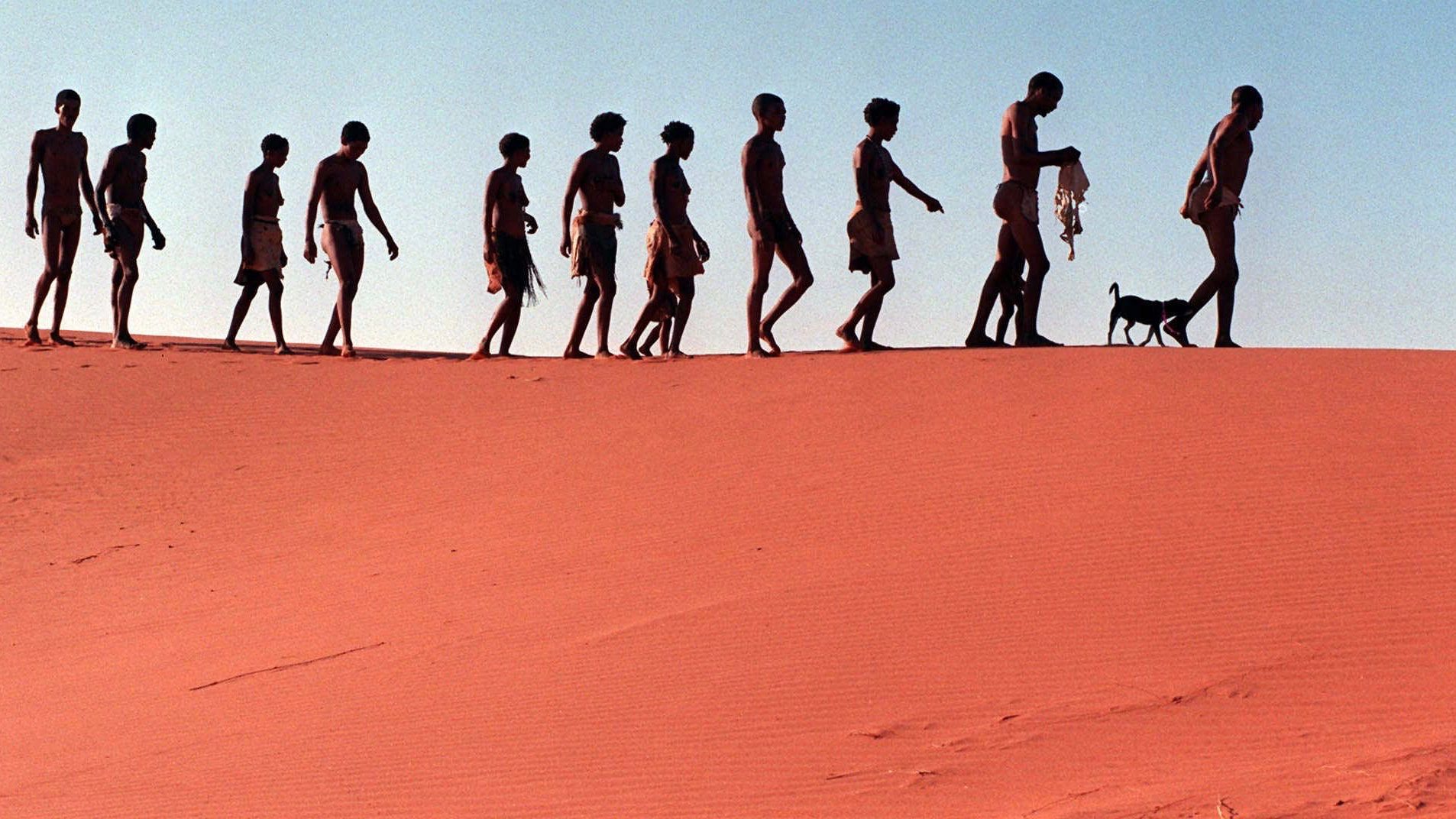 Bushmen walk on the dunes in the Kalahari Gemsbok Park in South Africa, Jan. 23, 1999, to visit a ancestral burial site. Though much of the land redistribution process has been slow and dogged by legal fights, the Khomani claim for a huge piece of land which was taken from under them during colonialism and apartheid, is close to being settled. (AP Photo Obed Zilwa)