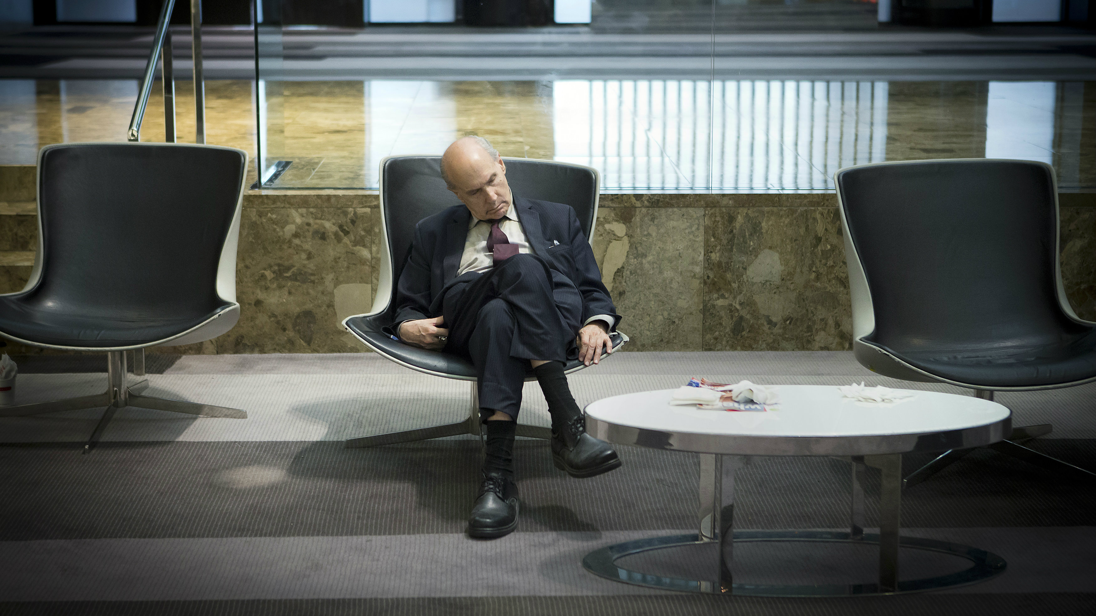 A businessman takes a mid-day nap in the lobby of a midtown hotel in the Manhattan borough of New York August 1, 2014. REUTERS/Carlo Allegri (UNITED STATES - Tags: SOCIETY BUSINESS)