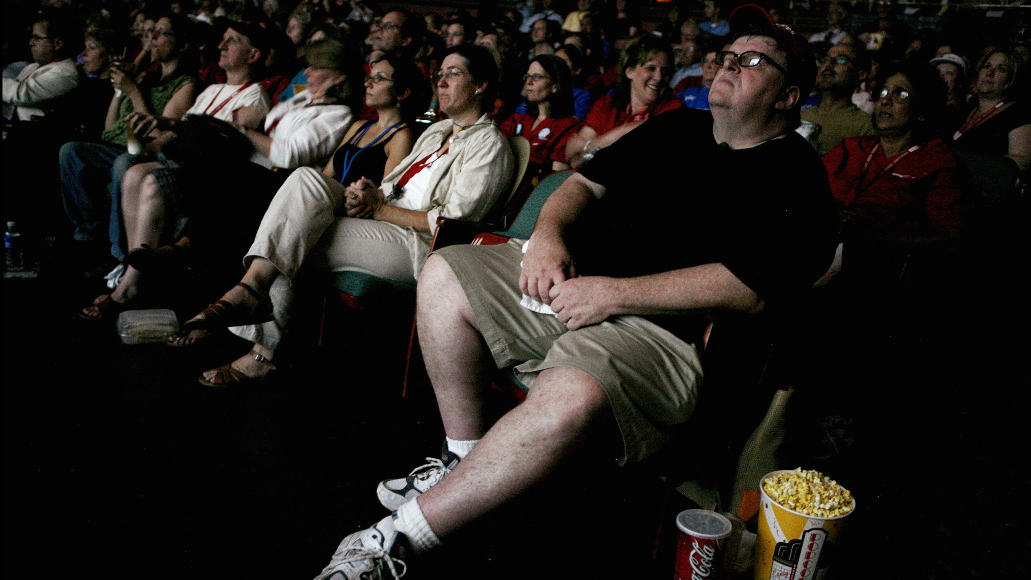 """Filmmaker Michael Moore watches his documentary """"SiCKO"""" during a special screening for the California Nurses Association (CNA) at the Crest Theater in Sacramento June 12, 2007. REUTERS/Max Whittaker (UNITED STATES) - RTR1QQM9"""