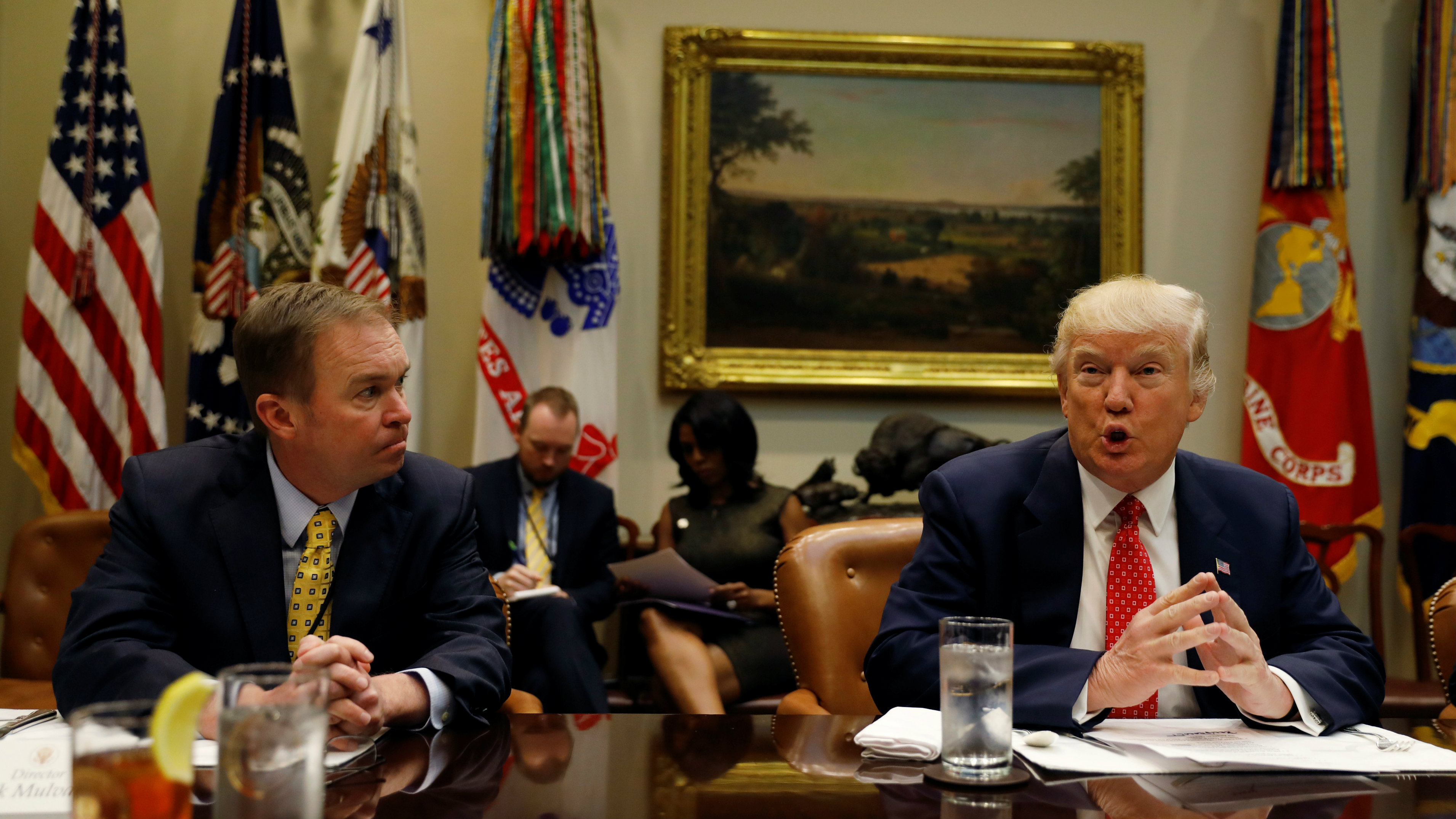 "Director of the Office of Management and Budget Mick Mulvaney (L) listens to U.S. President Donald Trump speak during a ""strategic initiatives"" lunch at the White House in Washington, U.S., February 22, 2017. REUTERS/Kevin Lamarque"