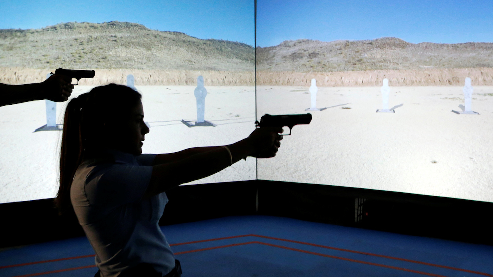 An Arab Israeli police recruit takes aim with her gun towards a screen displaying targets during a training exercise at Israeli police academy center in Beit Shemesh, Israel August 24, 2016. Picture taken August 24, 2016. REUTERS/Ammar Awad - RTX2N05O