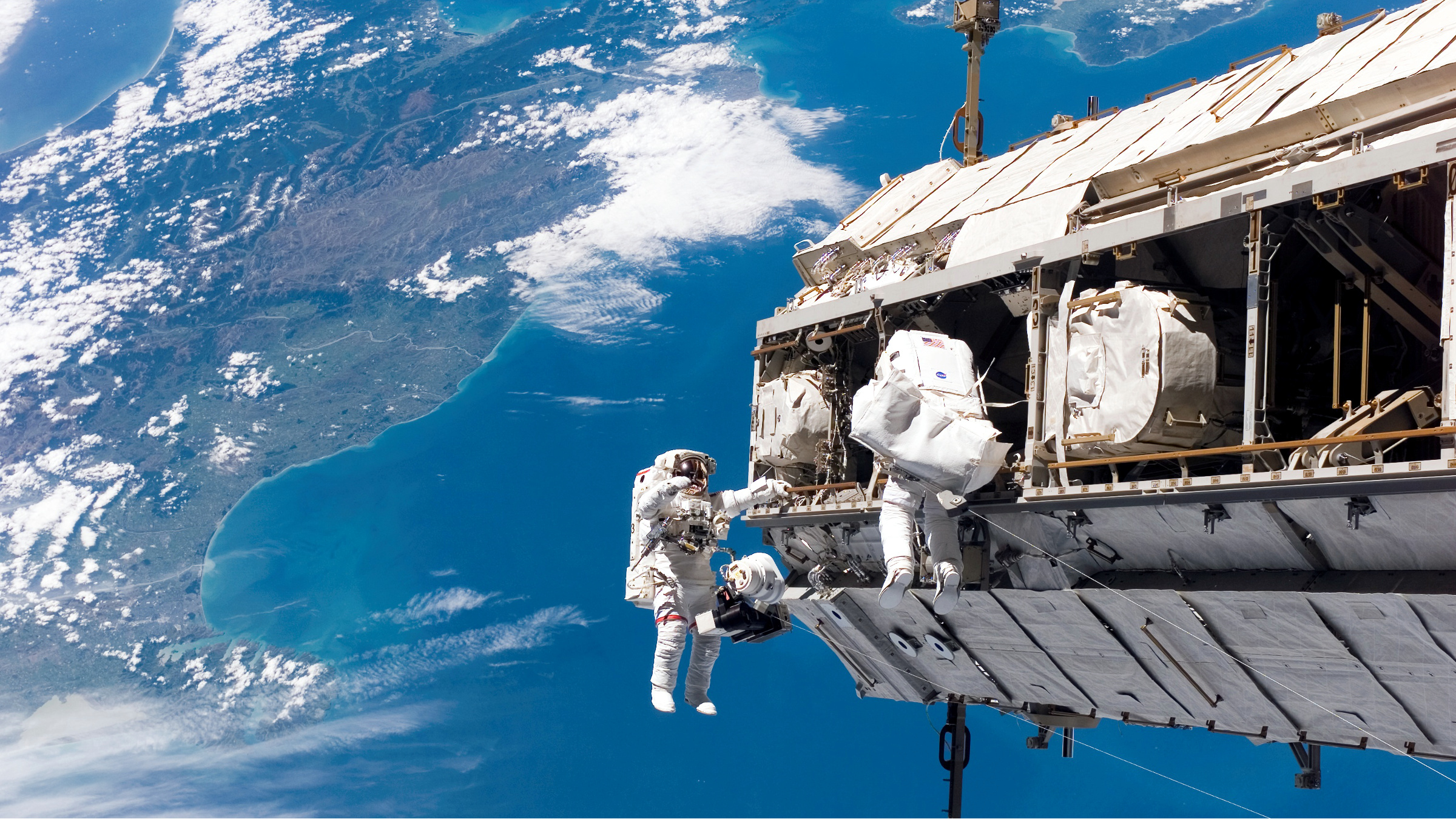 Two astronauts construct the International Space Station over New Zealand in 2006.