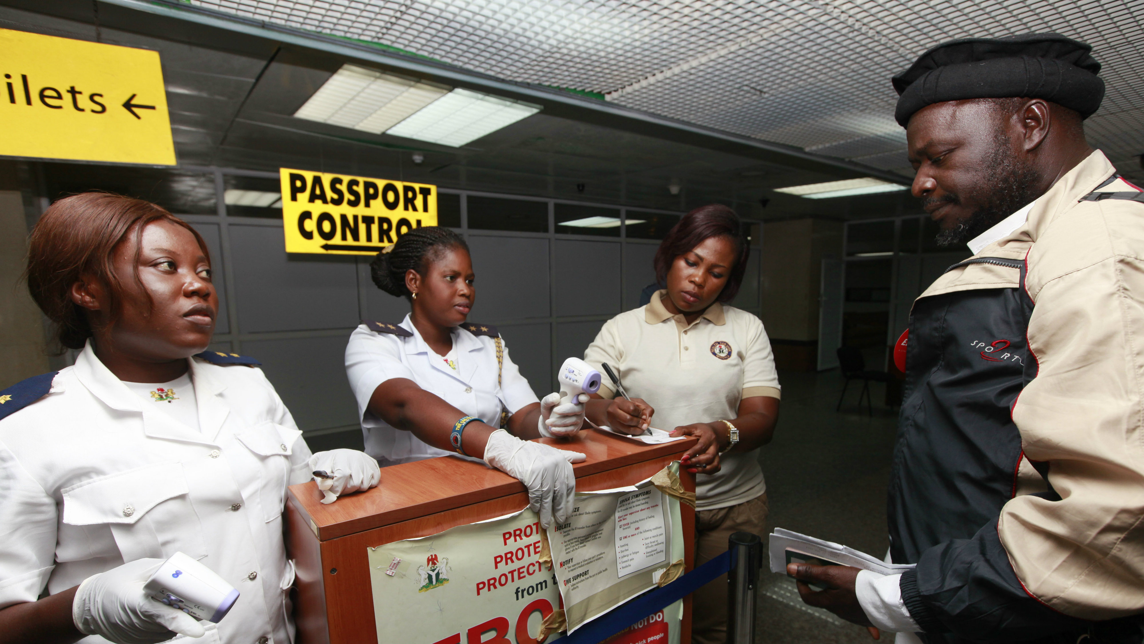 Health port officials uses a thermometer to screen passengers at the arrival hall of Murtala Mohammed International airport in Lagos, Nigeria Monday, Oct. 20, 2014.
