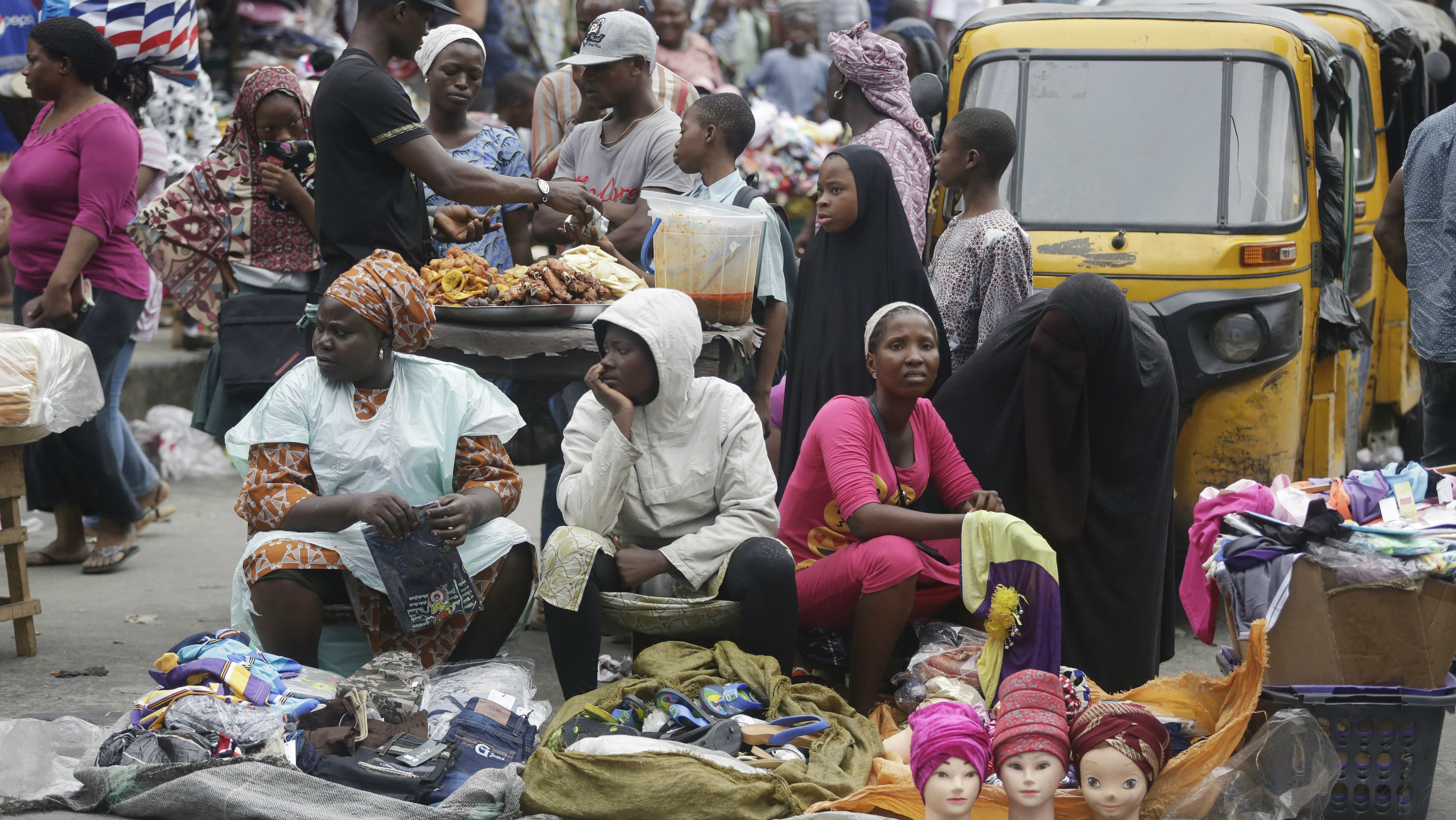 People crowd around the market stalls in Lagos, Nigeria, Monday June 20. 2016. Nigeria's currency plummeted Monday, losing value as the government floated the naira for the first time in the history of the oil-producing nation.