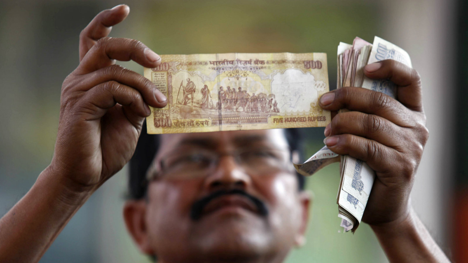 A worker at a fuel station checks a Rs500 note in Kolkata.