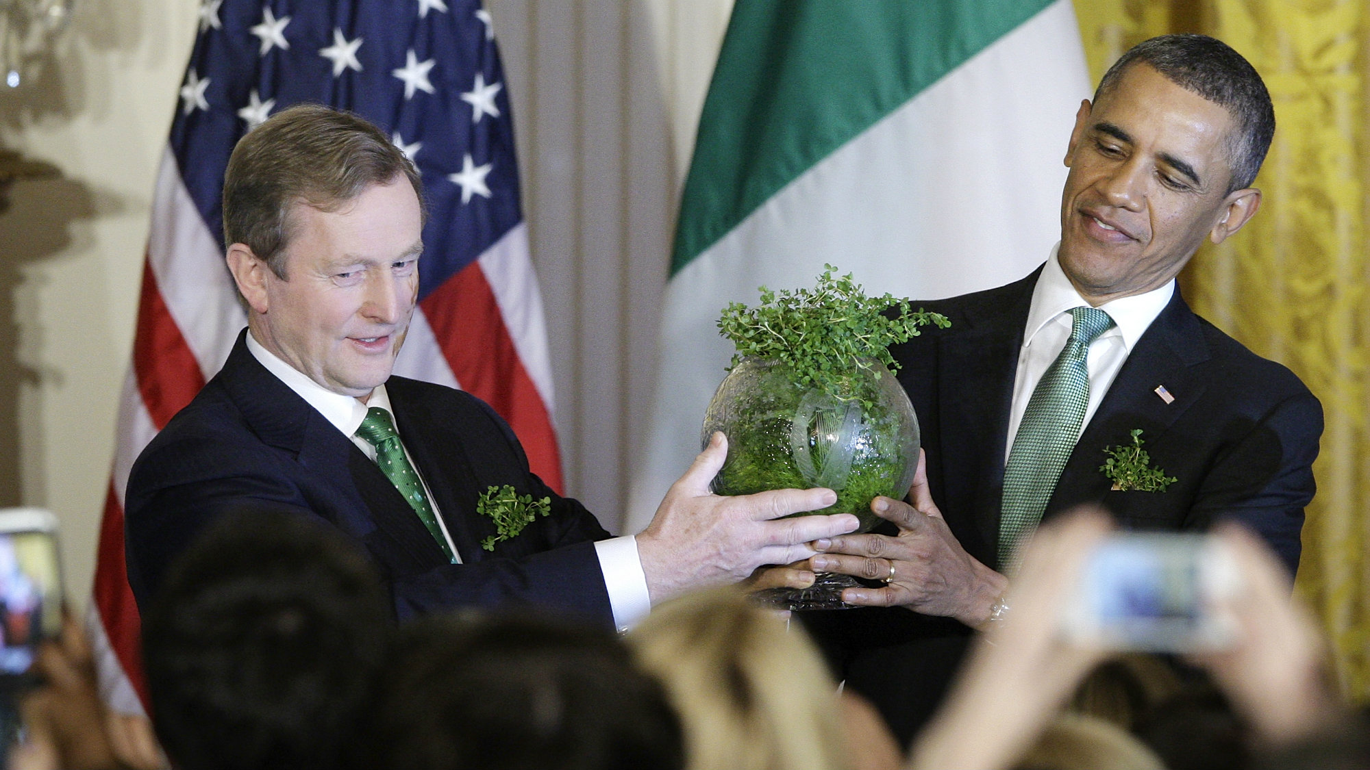 Irish Prime Minister Enda Kenny (L) gives a gift of an etched bowl filled with traditional shamrocks to U.S. President Barack Obama during a St. Patrick's Day reception at the White House in Washington, March 19, 2013.