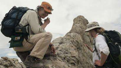 Two female paleontologists are examining rock remains.