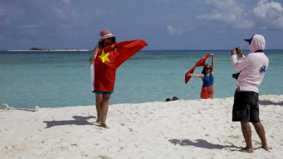 Chinese tourists take souvenir photos with the Chinese national flag as they visit Quanfu Island, one of Paracel Islands of Sansha prefecture of southern China's Hainan province in the South China Sea.
