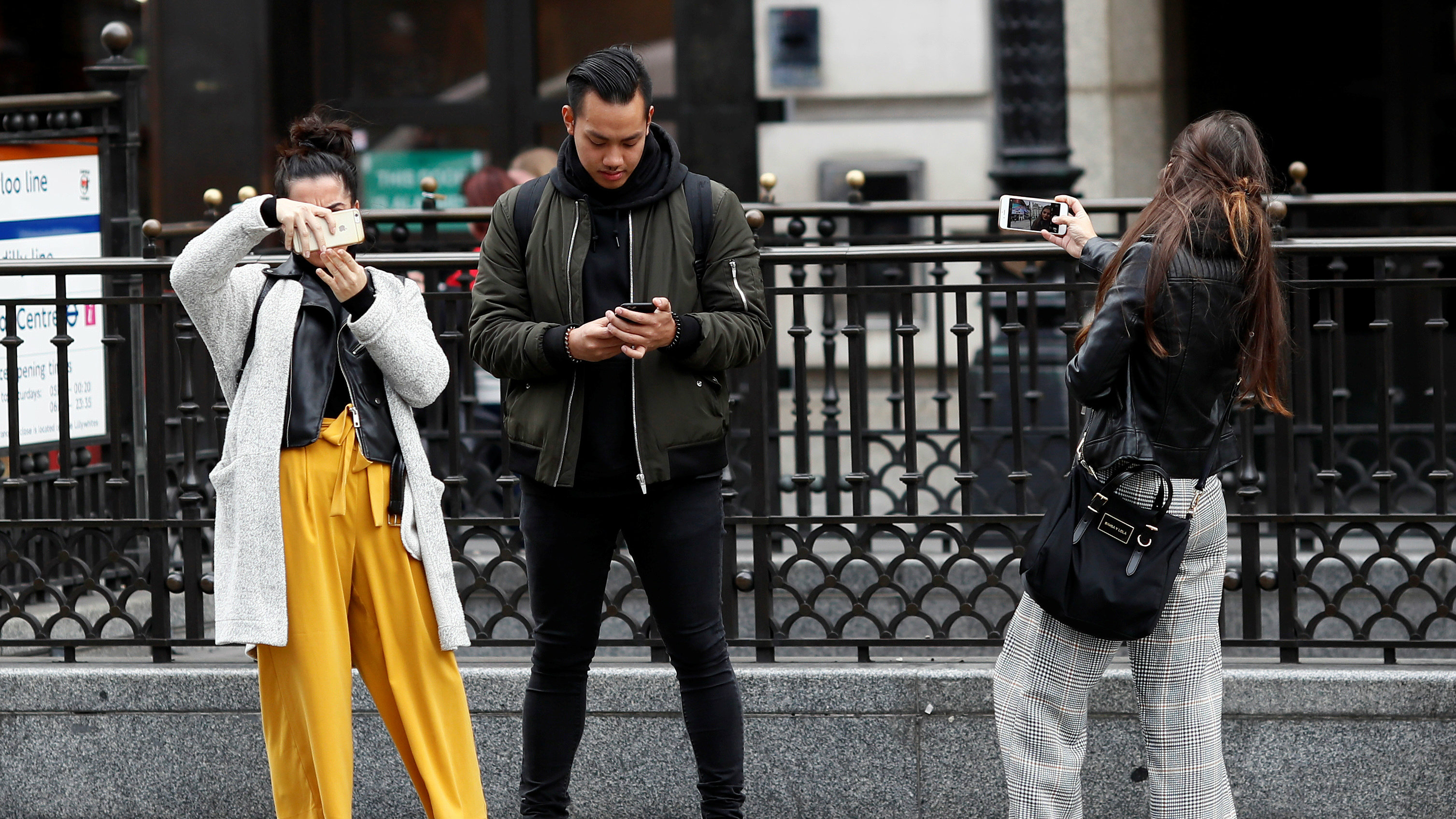 People look at their mobile phones at Piccadilly Circus in London