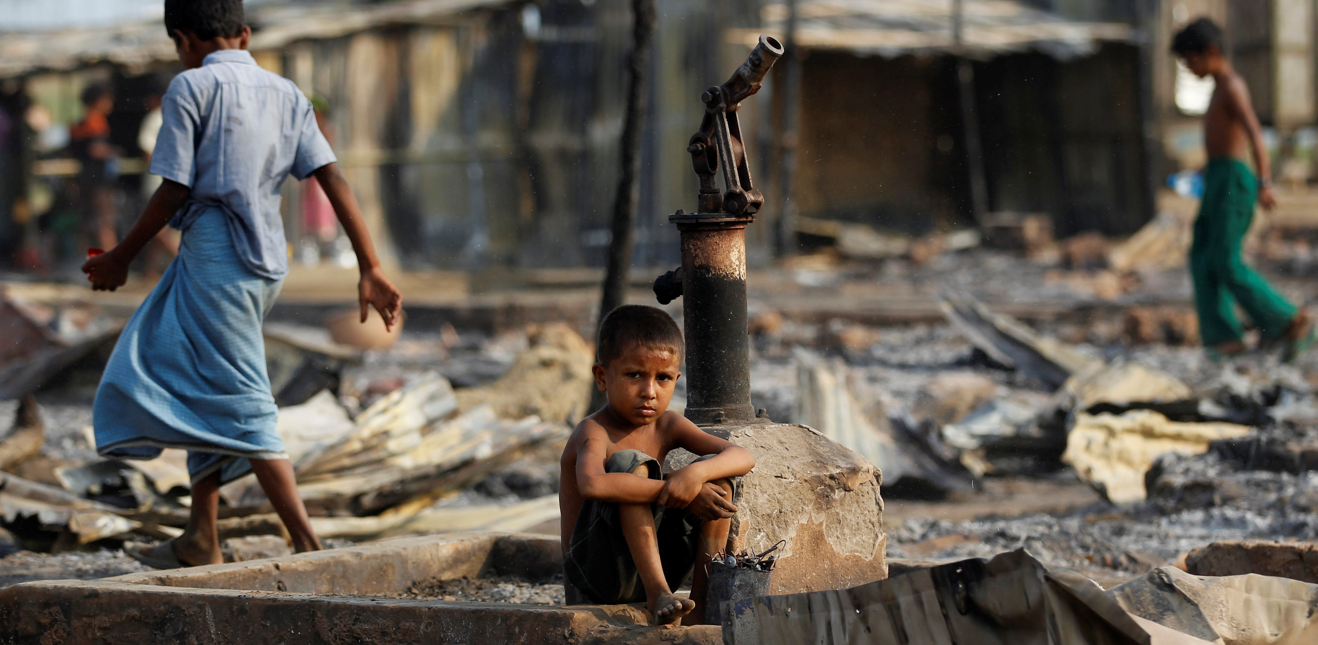 A boy sit in a burnt area after fire destroyed shelters at a camp for internally displaced Rohingya Muslims in the western Rakhine State near Sittwe