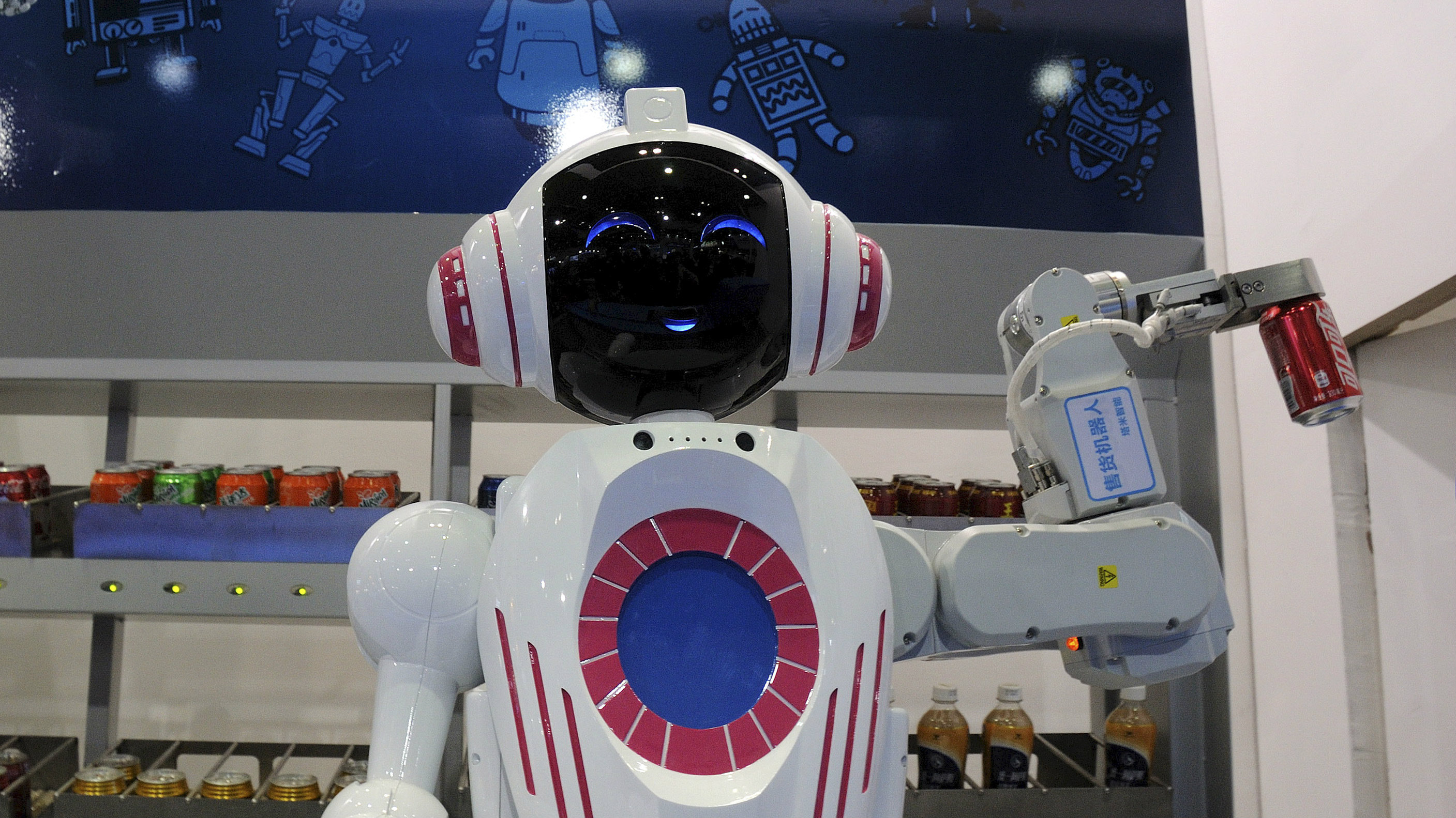 A sales assistant robots holds can of coke