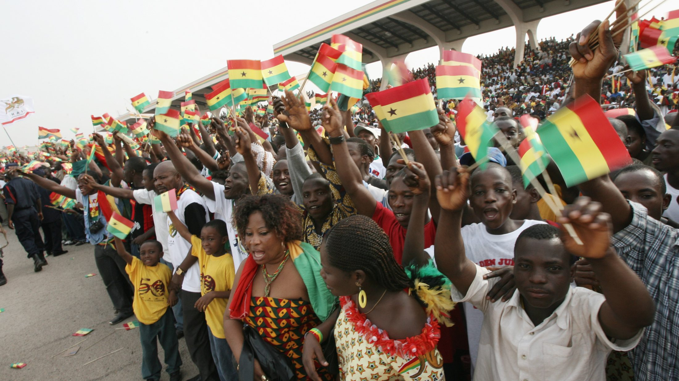 People raise national flags at Independence Square during celebrations marking the 50th anniversary of the country's independence in Accra