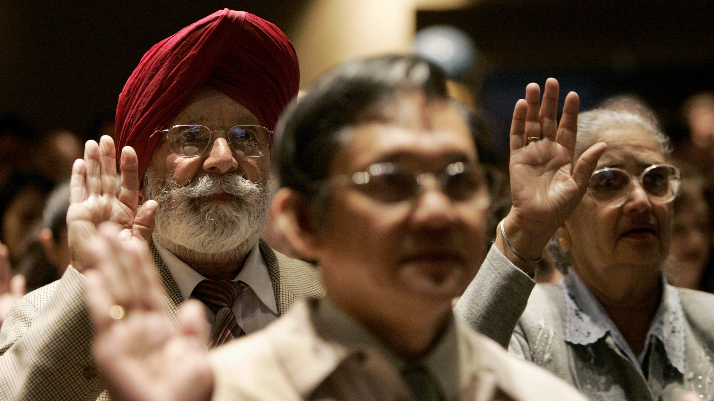 Gurdarshan Gill (rear L) of India takes the oath to become a U.S. citizen during a naturalization ceremony, with more than 1,400 people from 100 countries becoming new U.S. citizens, in San Francisco, California May 22, 2007.  REUTERS/Robert Galbraith  (UNITED STATES) - RTR1PZAC