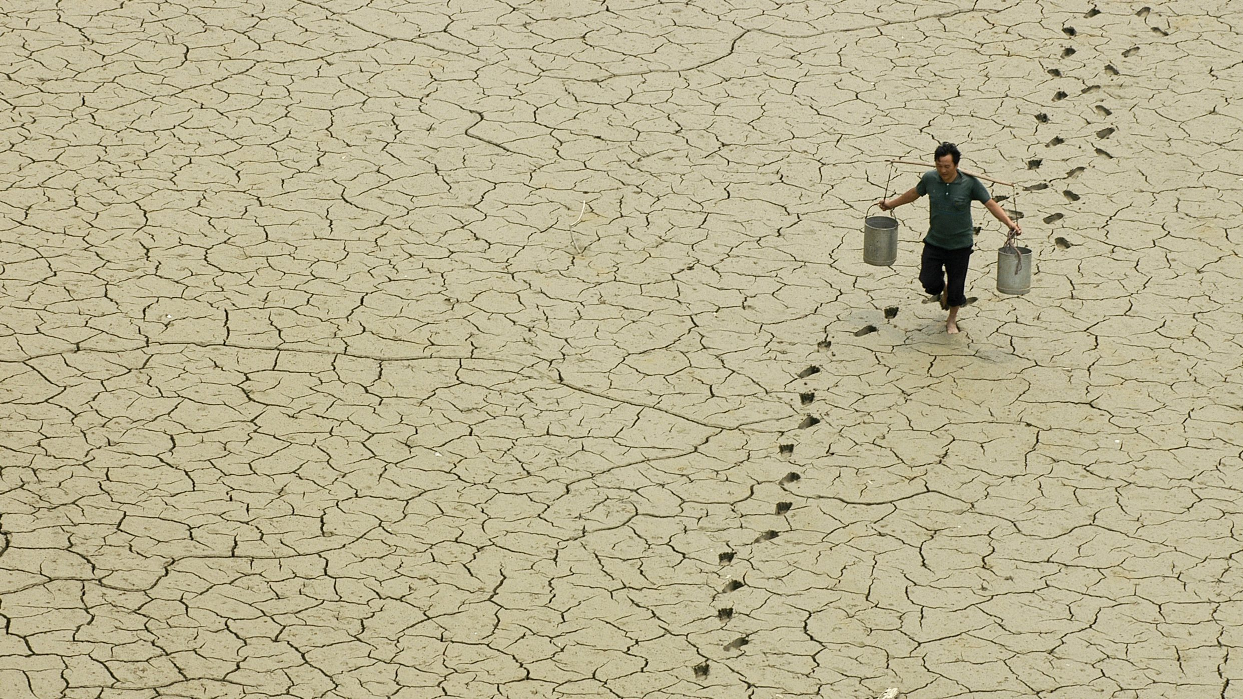 A farmer walks on a dried-up pond on the outskirts of Baokang, central China's Hubei province, June 10, 2007. REUTERS/Stringer (CHINA) CHINA OUT - RTR1QNJ3