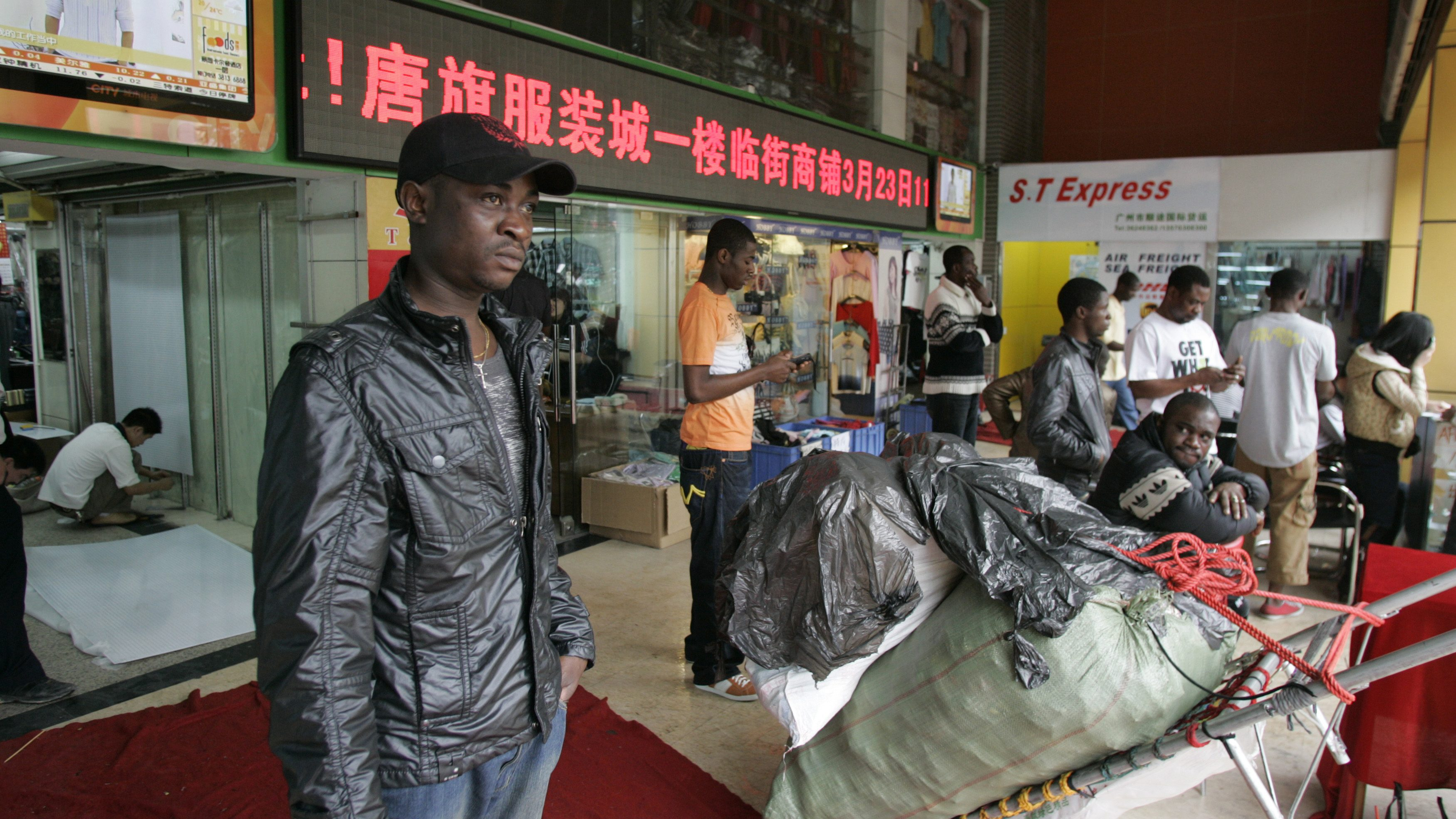 An African man stands near a shopping mall in the southern Chinese city of Guangzhou in Guangdong province March 27, 2009. In the past few years, tens of thousands of African and Arab traders have thronged to export hubs like Guangzhou and Yiwu to seek their fortunes, sourcing cheap China-made goods back home to massive markups in a growing, lucrative trade. Picture taken March 27, 2009. To match feature