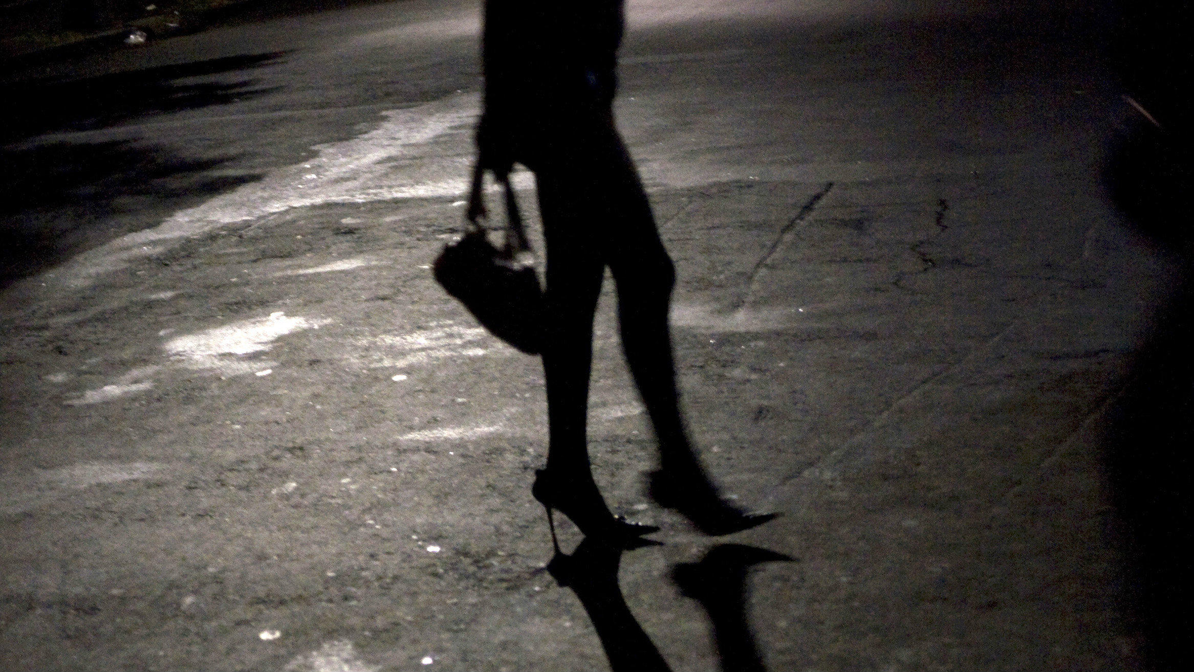 A prostitute crosses the street waiting to be picked up by customers in passing cars.