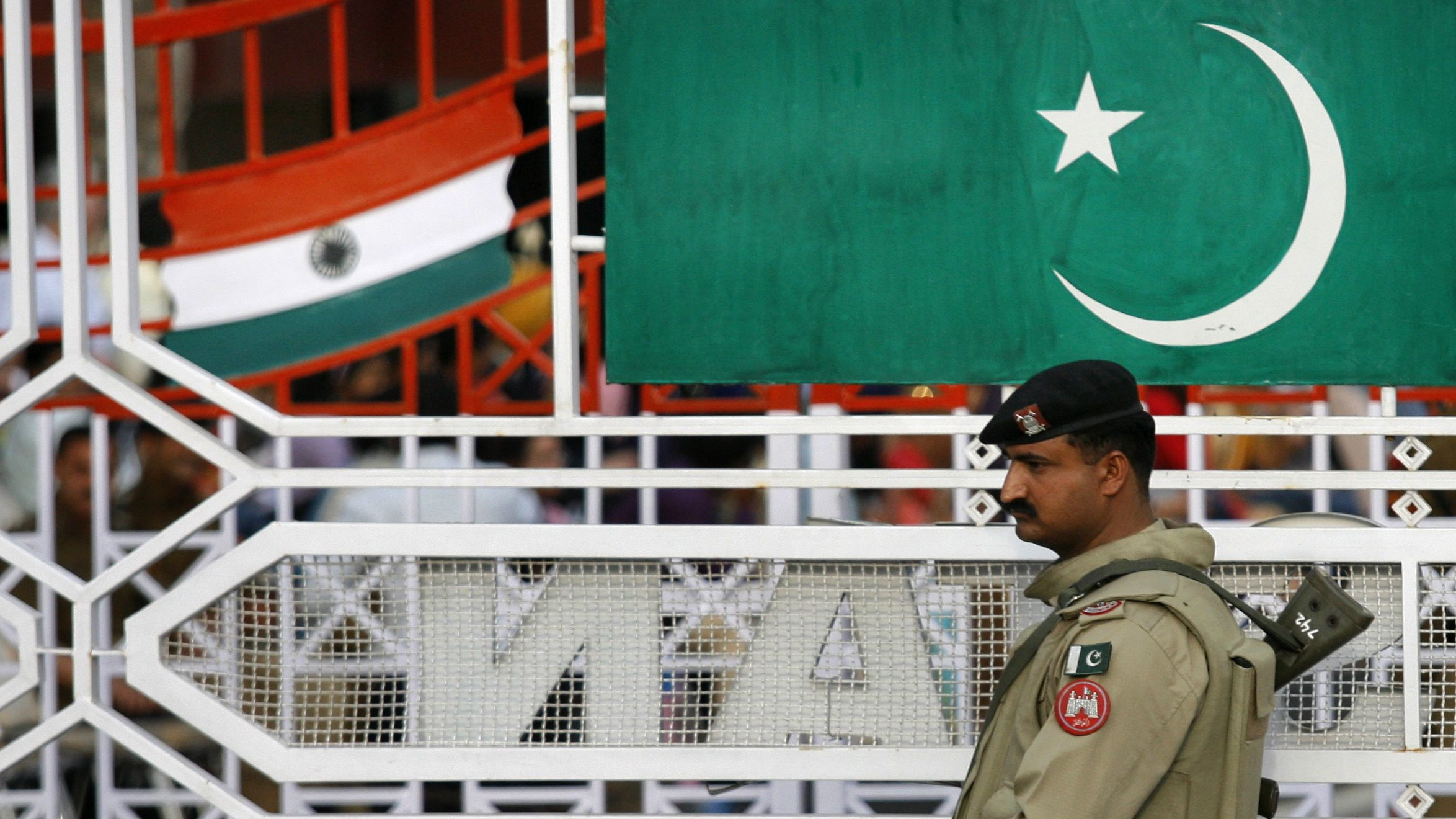 """A Pakistani Ranger stands near the Pakistani flag and Indian flag (L) during a daily parade at the Pakistan-India joint check post at Wagah border, on the outskirts of Lahore February 26, 2010. Commentators in both India and Pakistan greeted on Friday the first official talks between their countries since the 2008 Mumbai attacks with a degree of cynicism even though no breakthrough had been expected. The two nations' top diplomats met in a former princely palace in a heavily guarded New Delhi neighbourhood on Thursday and agreed to """"remain in touch"""" to build trust. REUTERS/Mohsin Raza   (PAKISTAN - Tags: POLITICS CIVIL UNREST MILITARY) - RTR2AY7W"""
