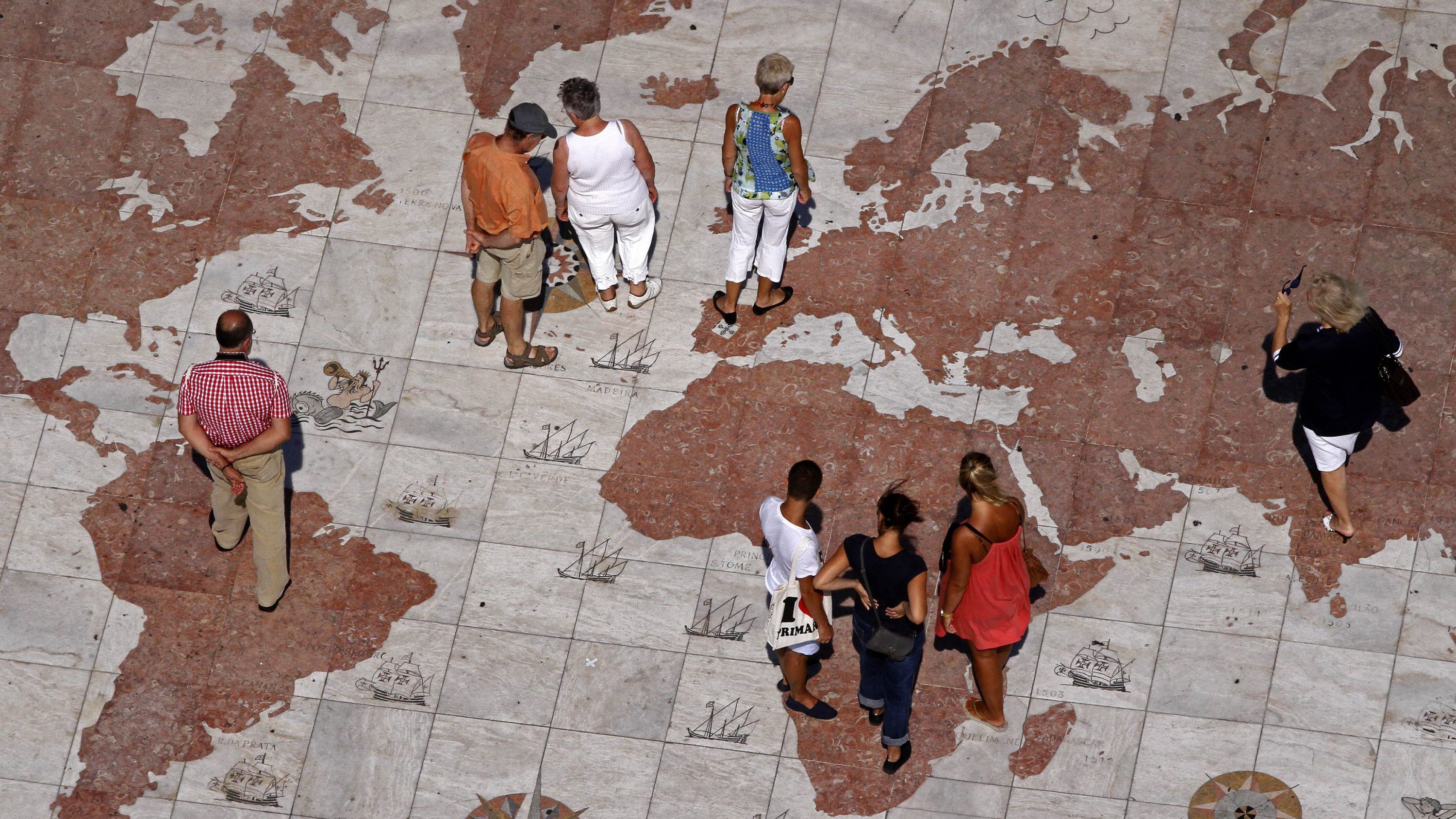 People walk over a world map engraved in marble in Lisbon September 14, 2011. Global markets have been roiled since the end of July by the twin fears of a recession in the United States and Europe's protracted debt woes, which have forced Greece, Ireland and Portugal to take bailouts and piled bond market pressure on Italy and Spain.