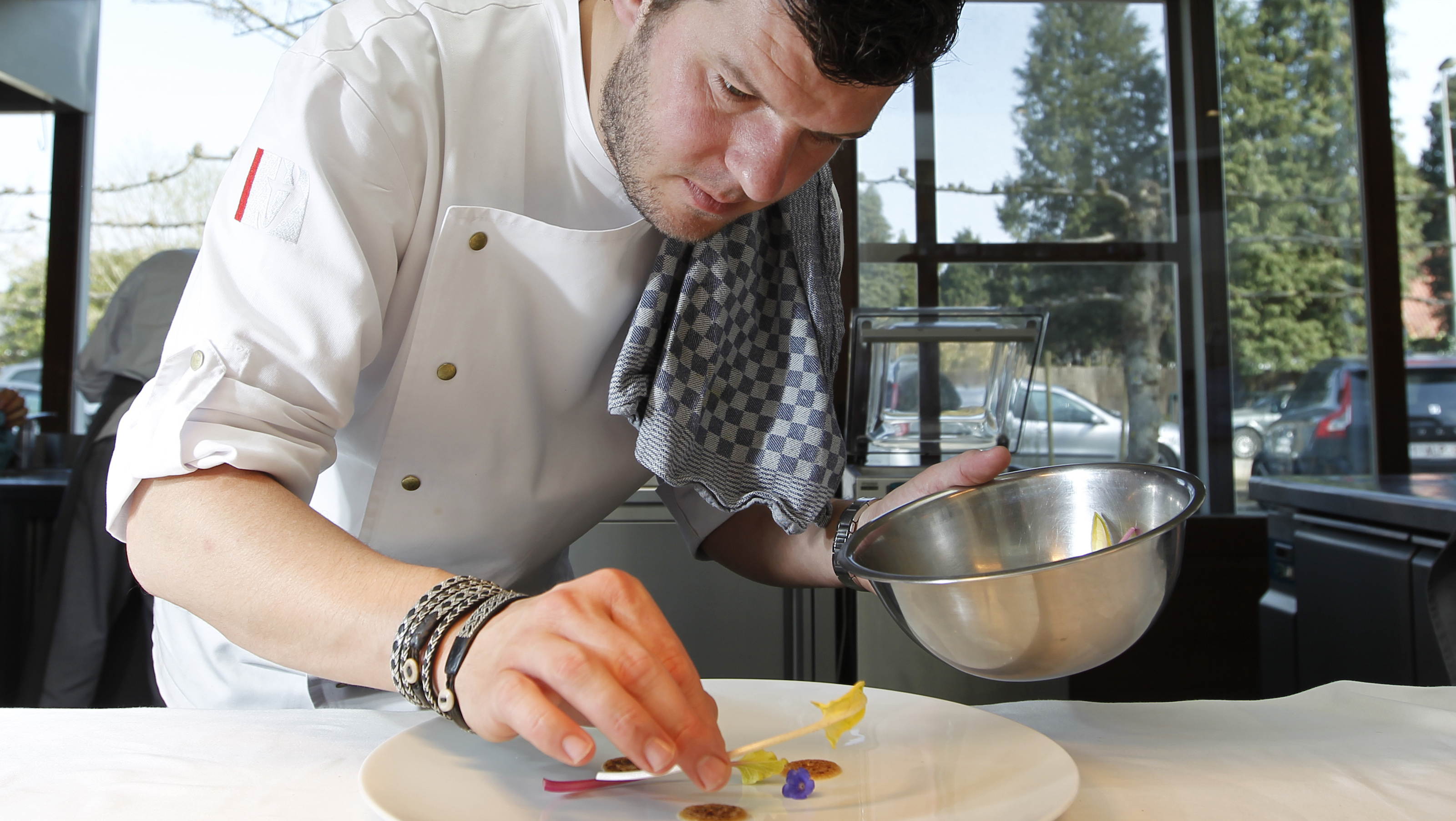 Belgian chef Gert De Mangeleer plates up a dish in the kitchen of Hertog Jan, the country's latest three-star Michelin restaurant, in Bruges March 29, 2012. De Mangeleer, 34, has taken Hertog Jan to the top of the culinary world with a cooking style based on fresh, local ingredients and perfection in preparation. He and Joachim Boudens, Hertog Jan's head sommelier, cultivate vegetables, flowers and herbs for the restaurant by themselves on a farm which they purchased two years ago.  Picture taken March 29, 2012. To match story BELGIUM-FOOD/  REUTERS/Francois Lenoir (BELGIUM - Tags: AGRICULTURE FOOD SOCIETY) - RTR30K14
