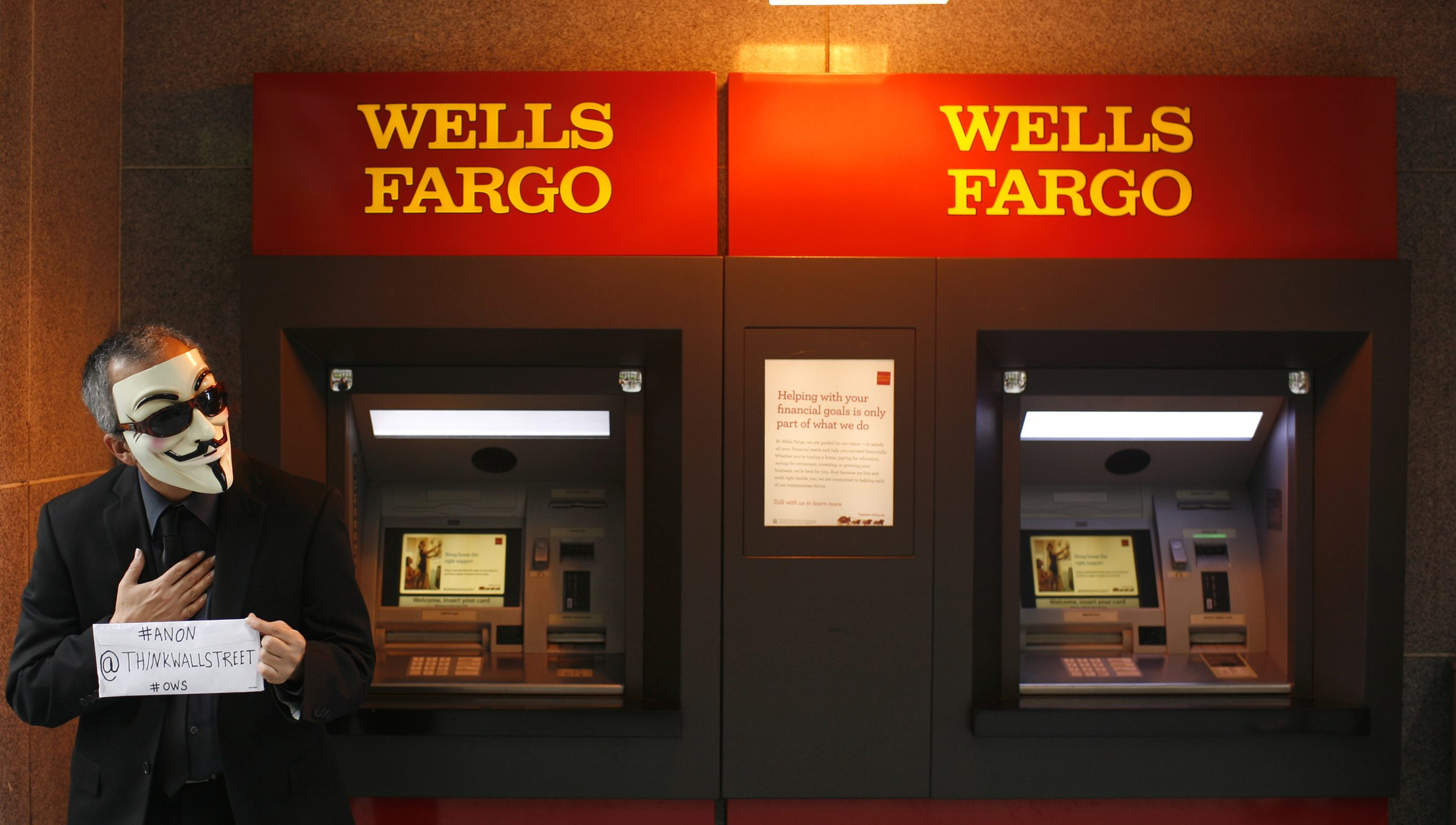 A demonstrator wearing a Guy Fawkes mask stands near an ATM machine during a protest outside of the Wells Fargo shareholders meeting in the Financial District in San Francisco, California April 24, 2012. REUTERS/Robert Galbraith  (UNITED STATES - Tags: BUSINESS CIVIL UNREST)