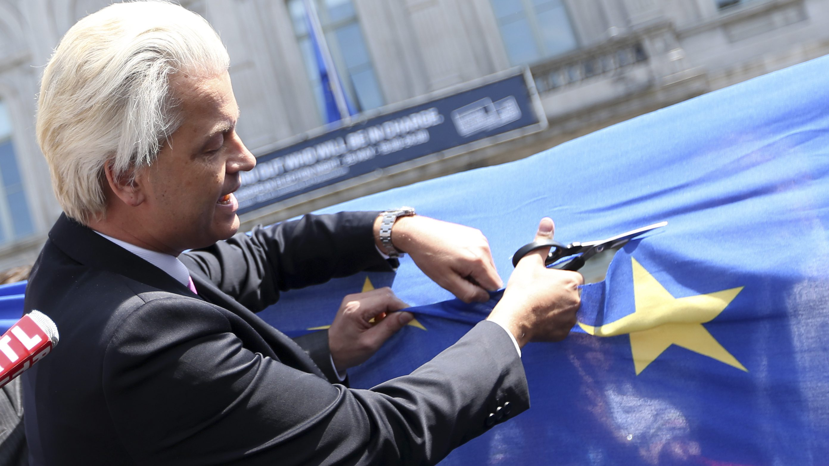 Dutch far-right Freedom Party leader Wilders cuts a star from the European Union flag during a demonstration in Brussels