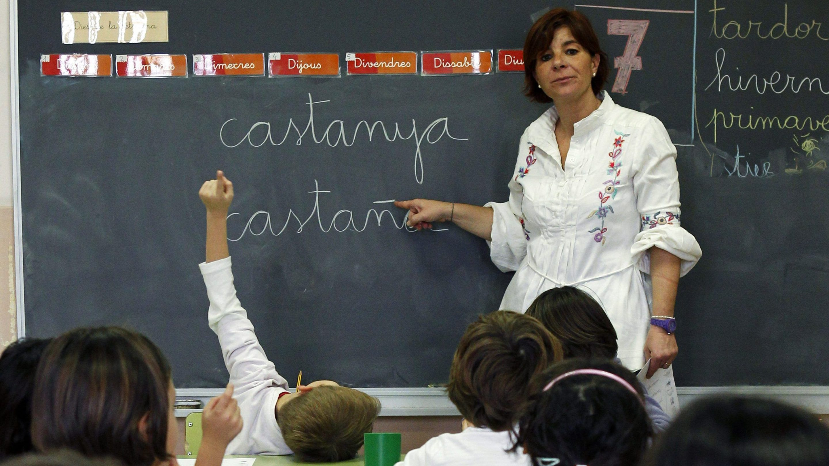 """School teacher Jorgina Fontboter points to a blackboard with words in Catalan and in Spanish during a language class at a public school in El Masnou, near Barcelona, December 14, 2012. The wealthy northeastern region of Catalonia last month dropped plans for a non-binding referendum on independence from Spain on Nov. 9 after a court declared such a vote against the constitution and had instead planned to hold a """"consultation of citizens"""" on the same day. Although Spanish Prime Minister Mariano Rajoy and politicians in Catalonia have called for dialogue over the region's status after the initial referendum plans were abandoned, tensions are still simmering before the Nov. 9 alternative vote. Picture taken December 14, 2014. REUTERS/Albert Gea (SPAIN) - Tags: POLITICS EDUCATION) ATTENTION EDITORS: PICTURE 13 OF 25 FOR WIDER IMAGE PACKAGE 'CATALONIA - THE CONSULTATION OF CITIZENS' TO FIND ALL IMAGES SEARCH 'CITIZENS' - RTR4D3U9"""