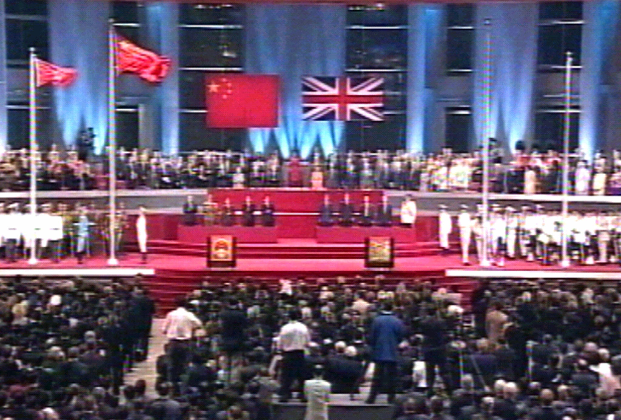 The Chinese and new Special Administrative Region (SAR) of Hong Kong (L) flags fly after they were raised during a handover ceremony June 30. Hong Kong reverted to Chinese rule at midnight June 30 after 156 years of British colonial administration.