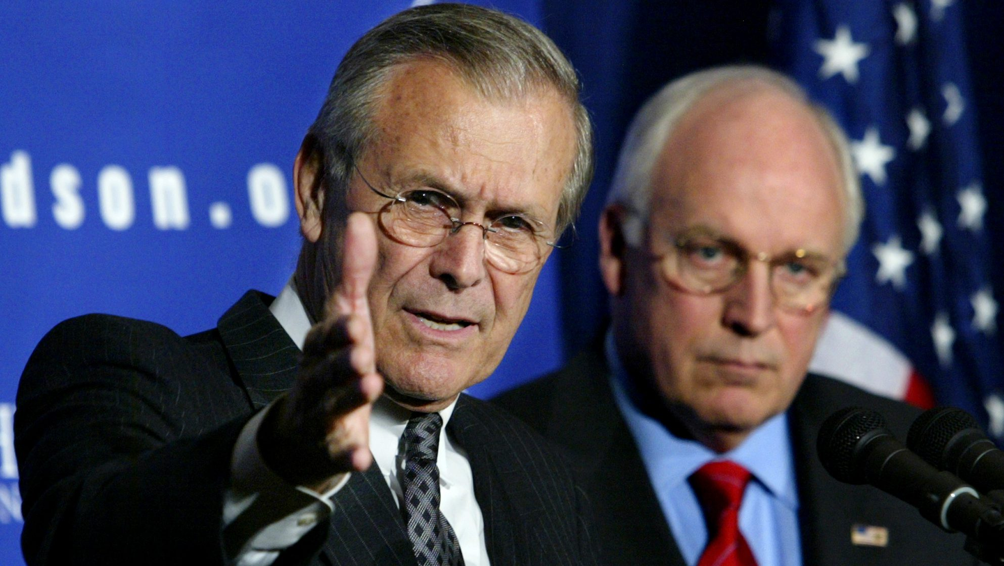 Rumsfeld and Cheney stand at a podium