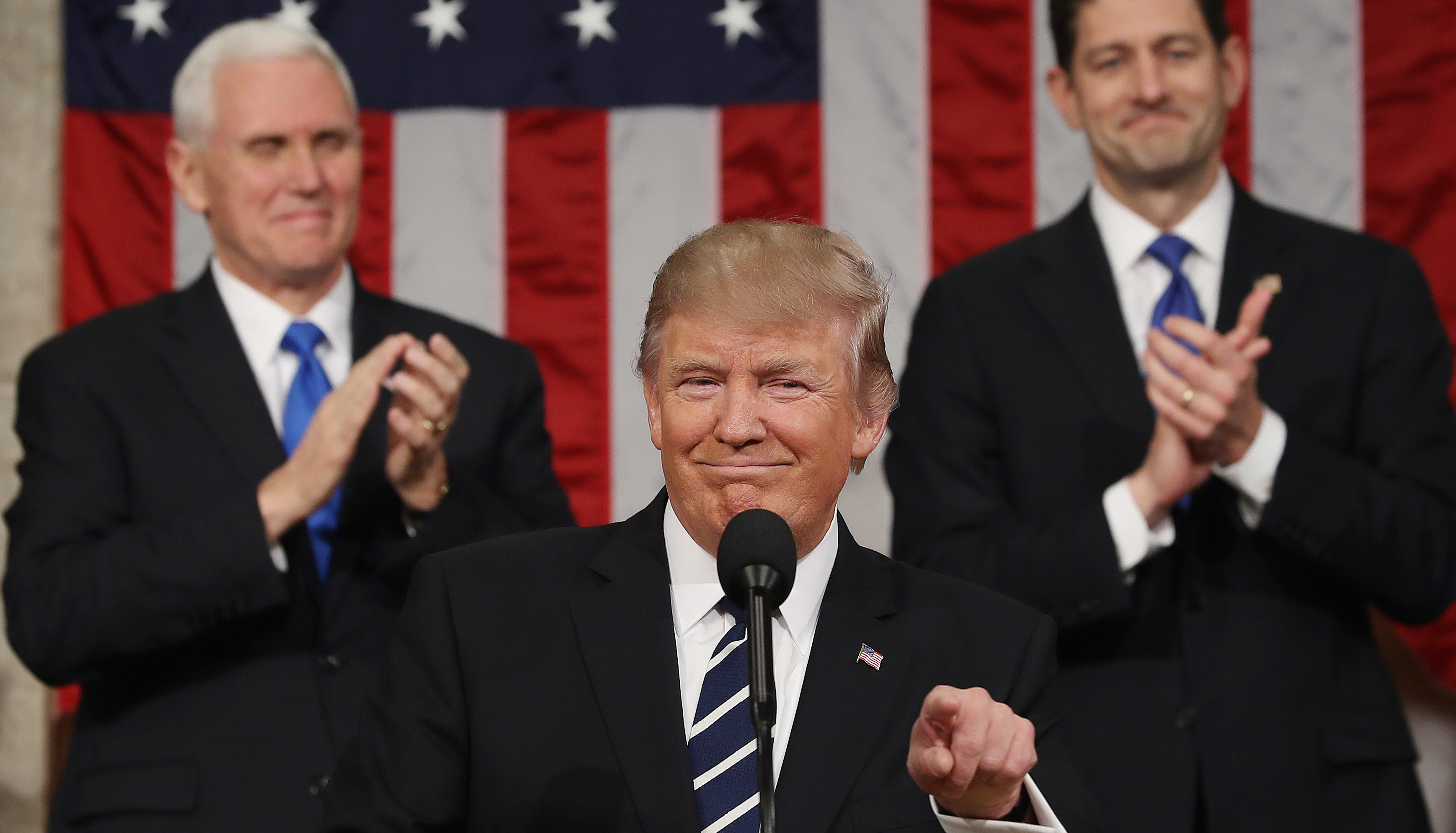 US Vice President Mike Pence (L) and Speaker of the House Paul Ryan (R) applaud as US President Donald J. Trump (C) arrives to deliver his first address to a joint session of Congress from the floor of the House of Representatives in Washington, DC, USA, 28 February 2017.