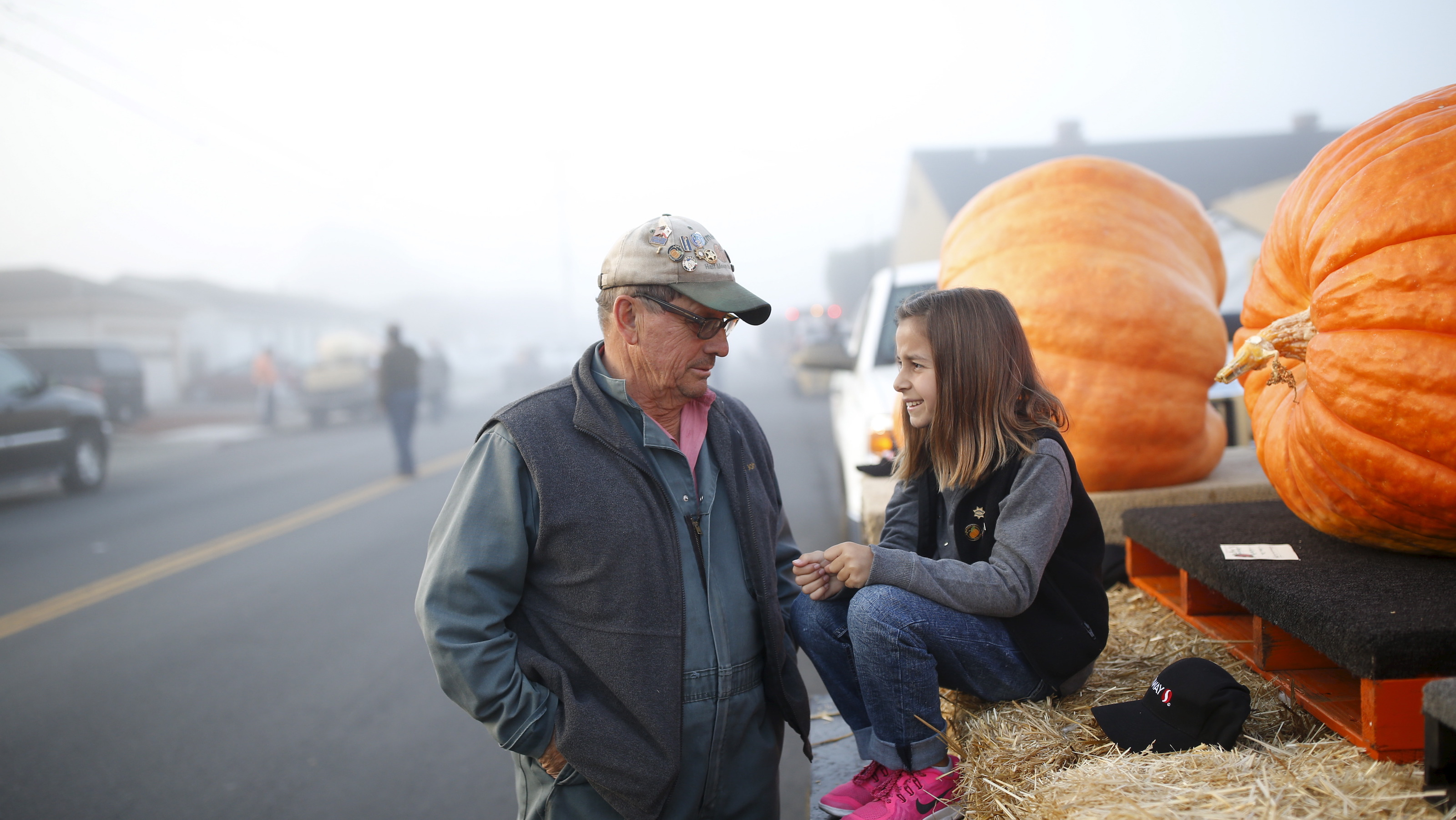 Farmer John (L) speaks with his granddaughter Delfina Bianchi, 7, as they wait next to their pumpkins during the annual Safeway World Championship Pumpkin Weigh-off in Half Moon Bay, California October 12, 2015. REUTERS/Stephen Lam - RTS44O6