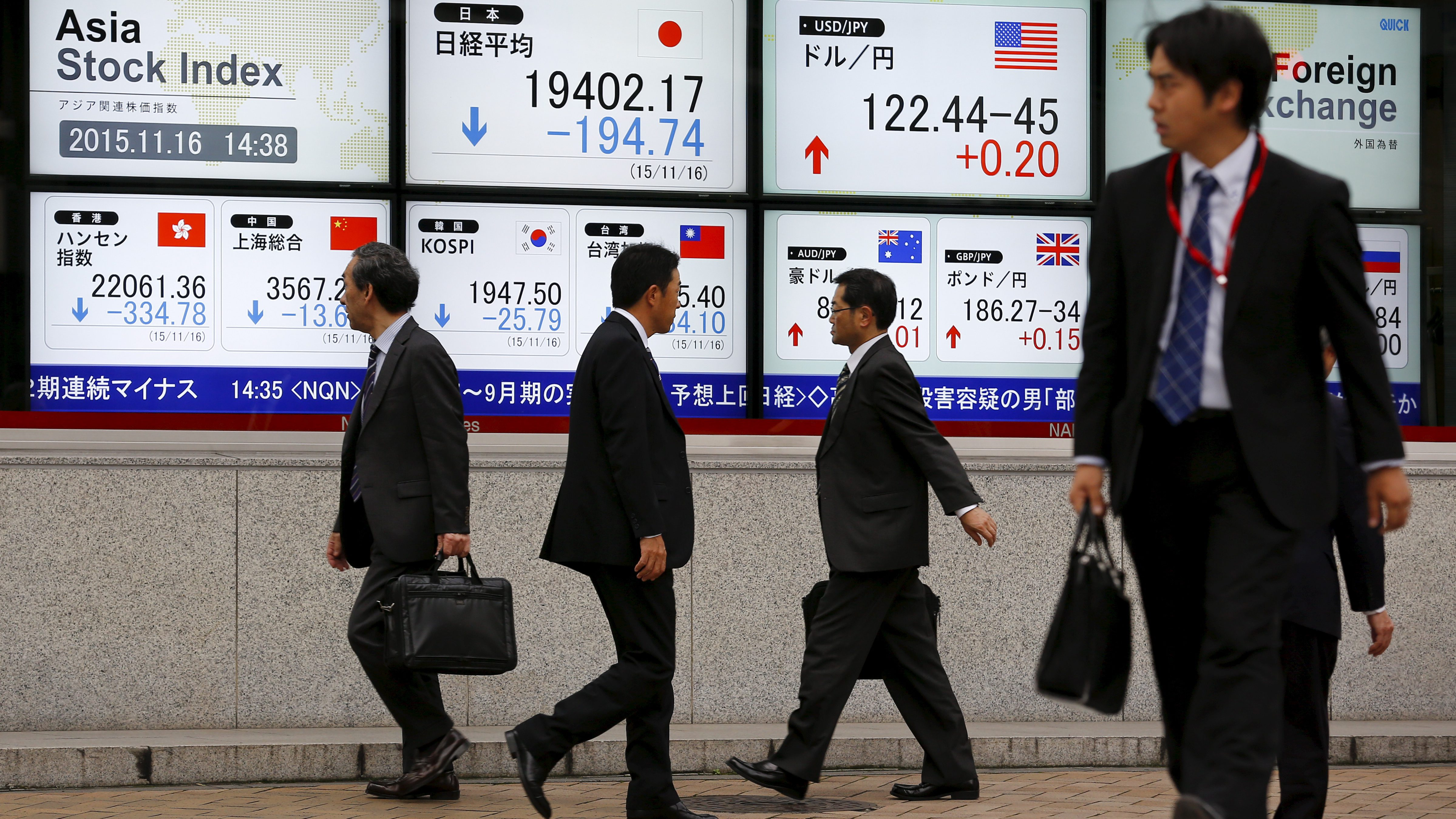 Businessmen walk past screens displaying market indices outside a brokerage in Tokyo, November 16, 2015.   REUTERS/Thomas Peter - RTS797O