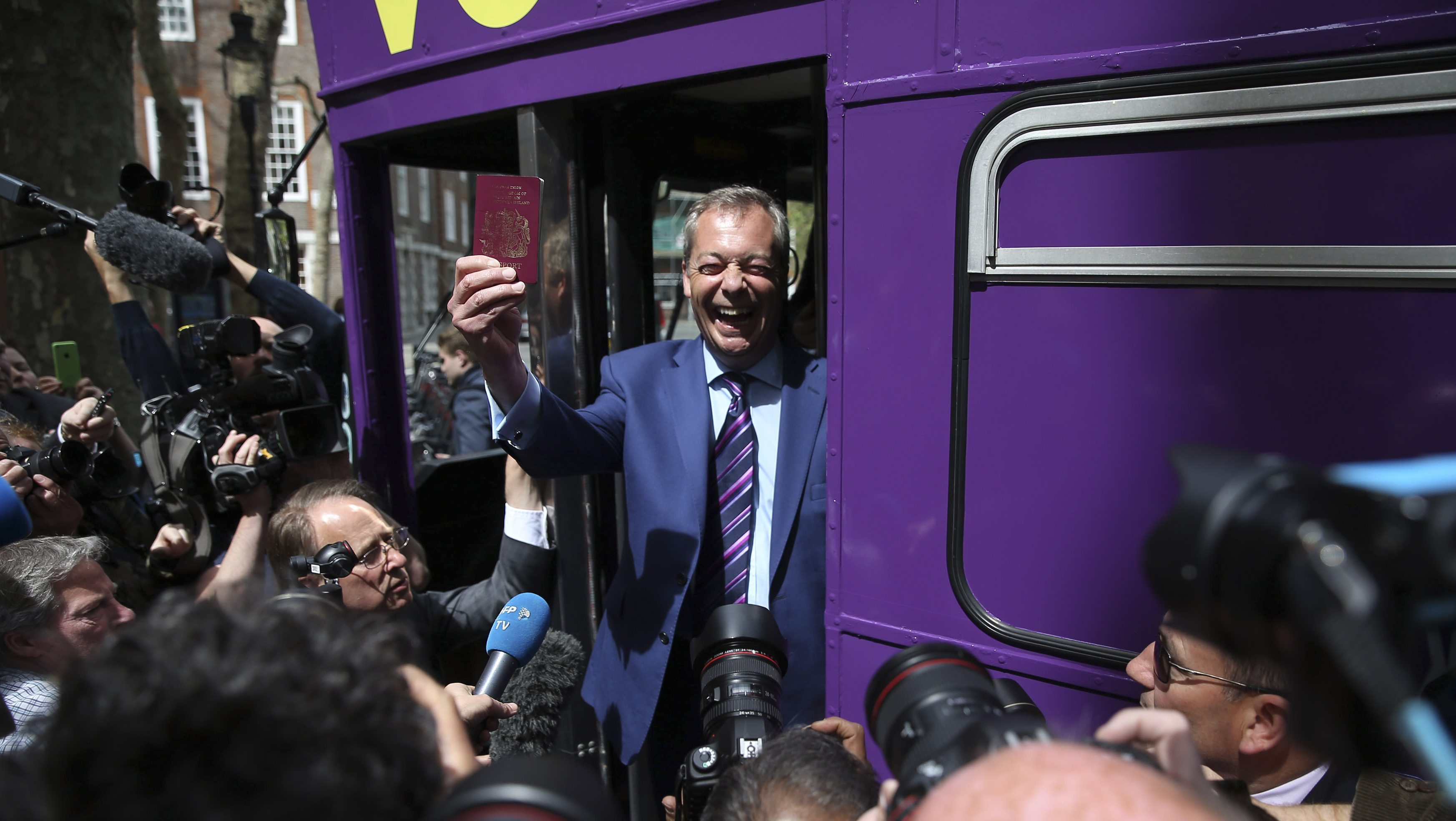 Leader of the United Kingdom Independence Party Nigel Farage holds his passport as he launches his party's EU referendum tour bus in London