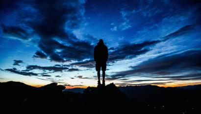 A man stands during sunrise on Kreuzjoch mountain in the Zillertal Alps