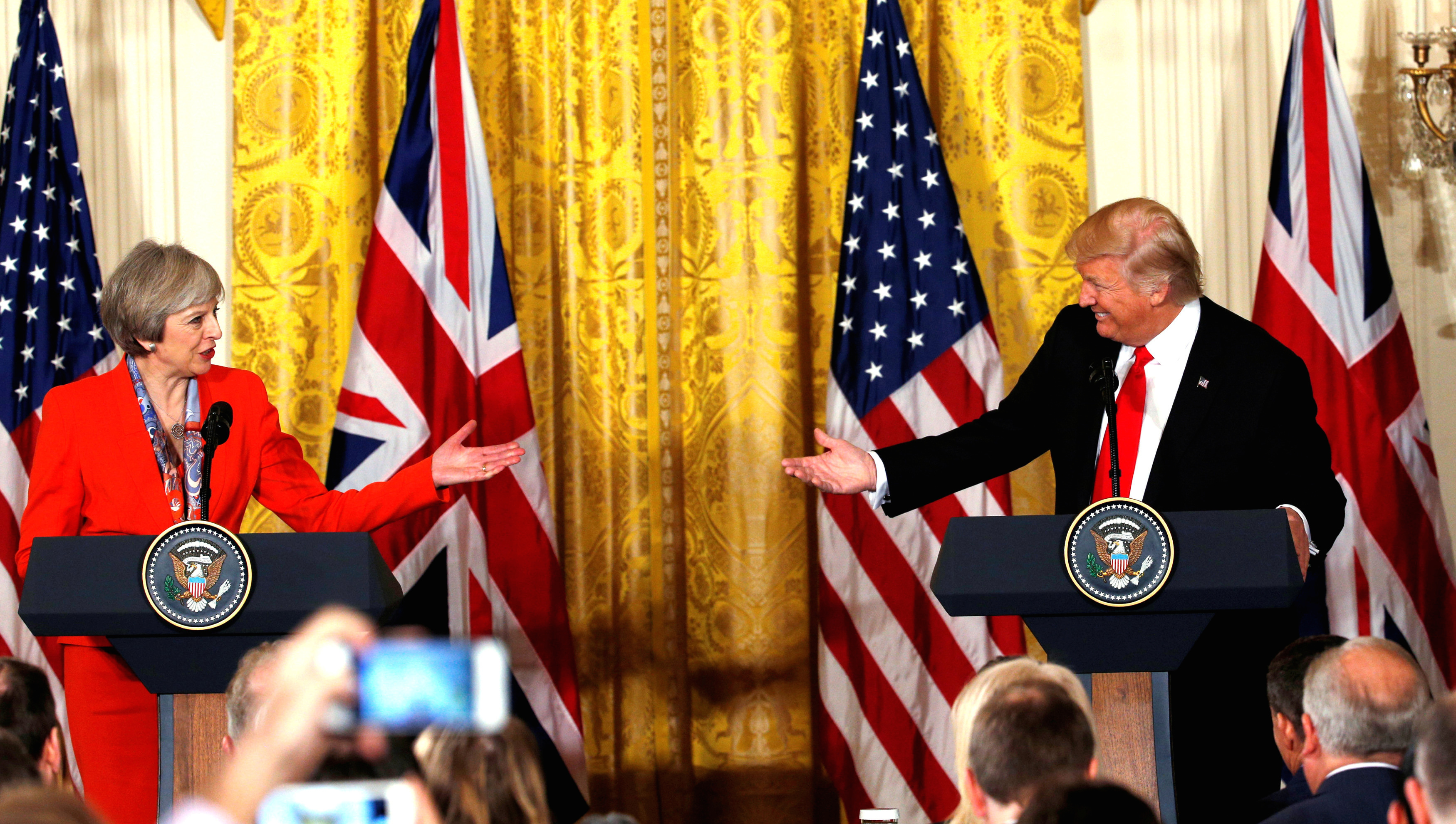 British Prime Minister Theresa May and U.S. President Donald Trump gesture towards each other during their joint news conference at the White House in Washington, U.S., January 27, 2017.