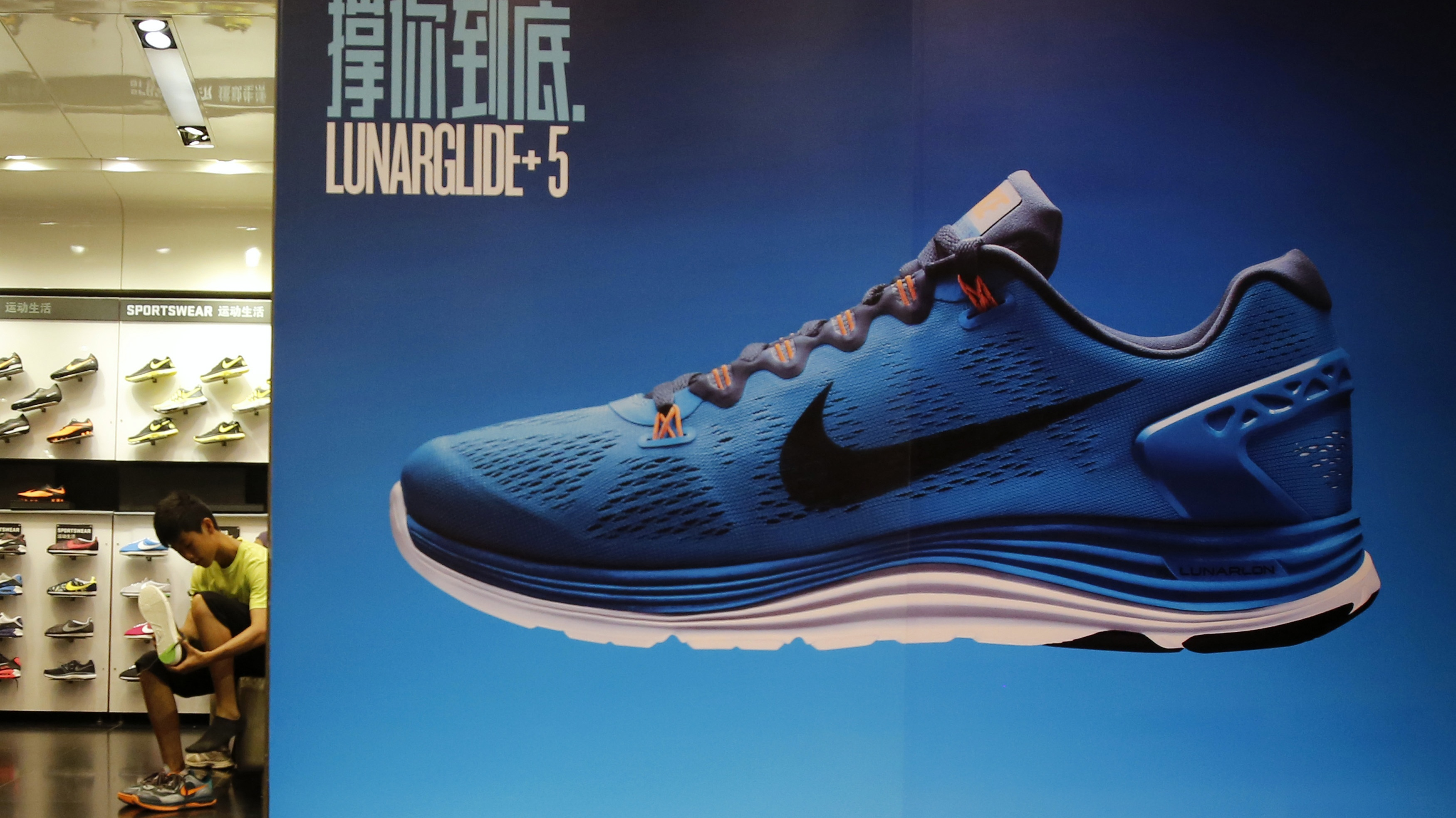 A customer tries on a pair of Nike shoes inside a shop at a shopping district in Beijing, August 6, 2013.