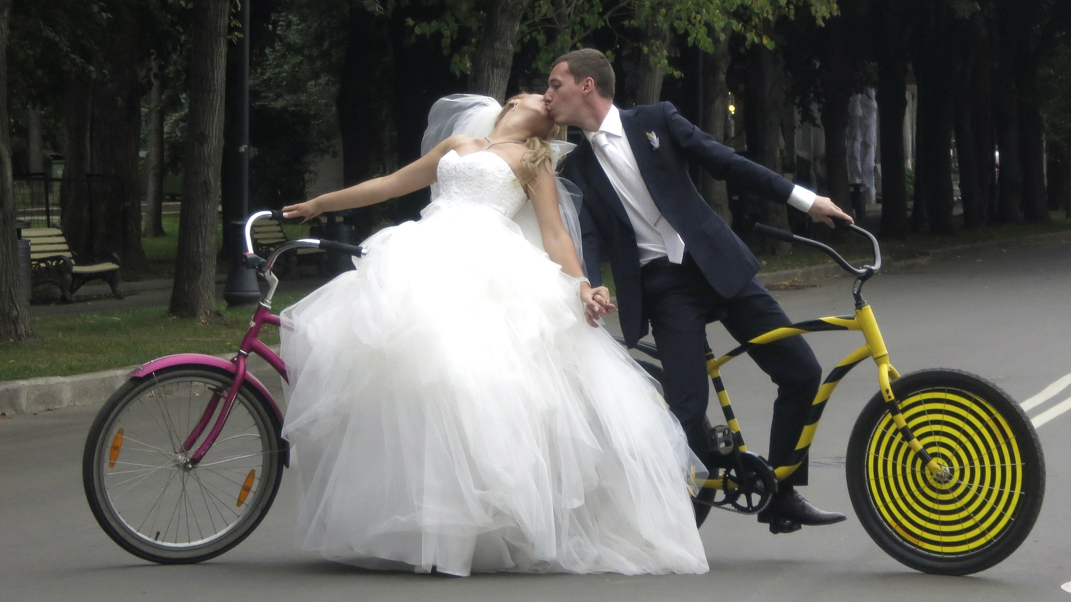 Yelena Babkini and her husband Boris kiss as they ride through Gorky Park on bicycles after having been...