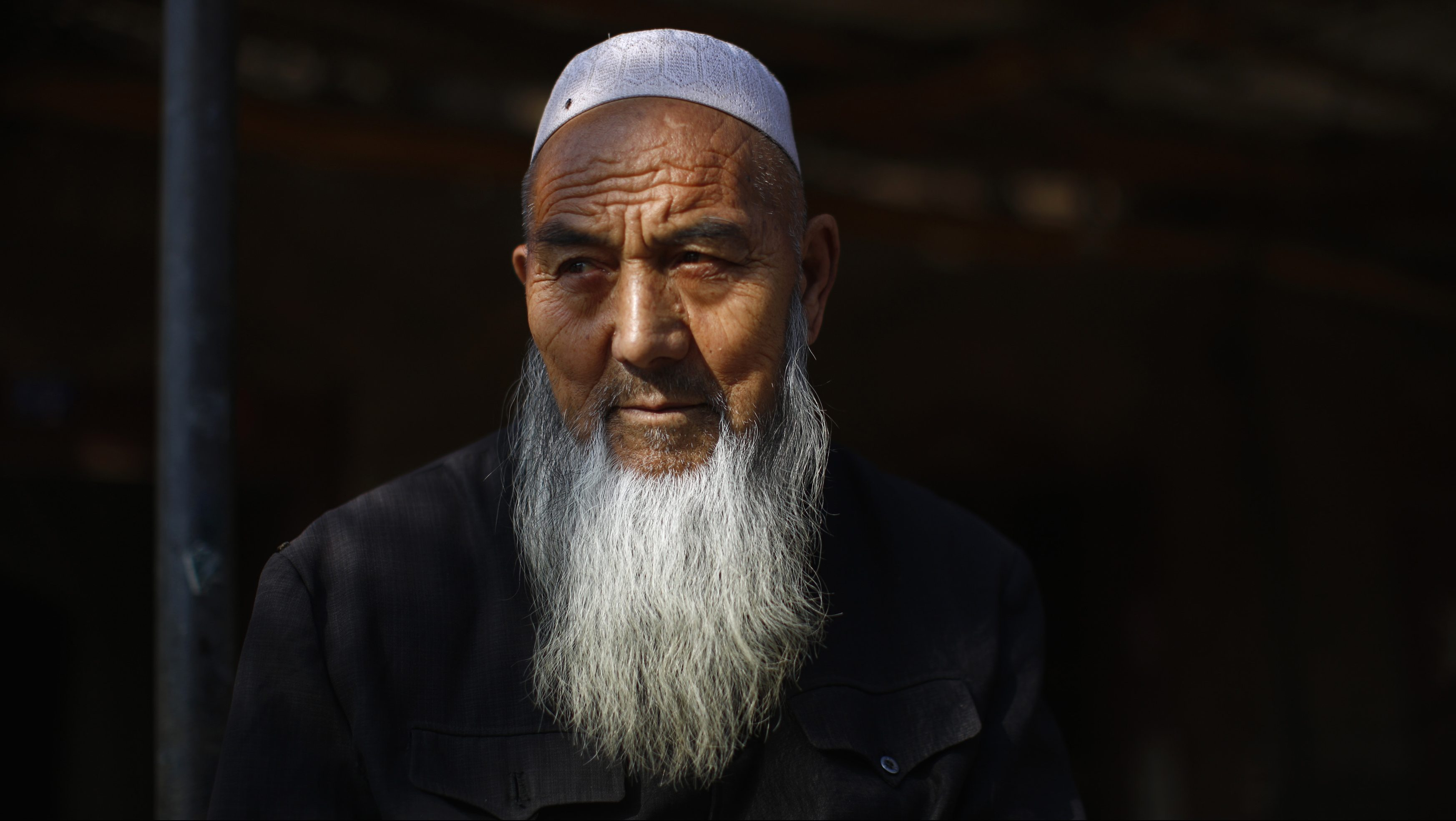 An ethnic Uighur man sits outside his house near a busy market in Turpan, Xinjiang province October 31, 2013