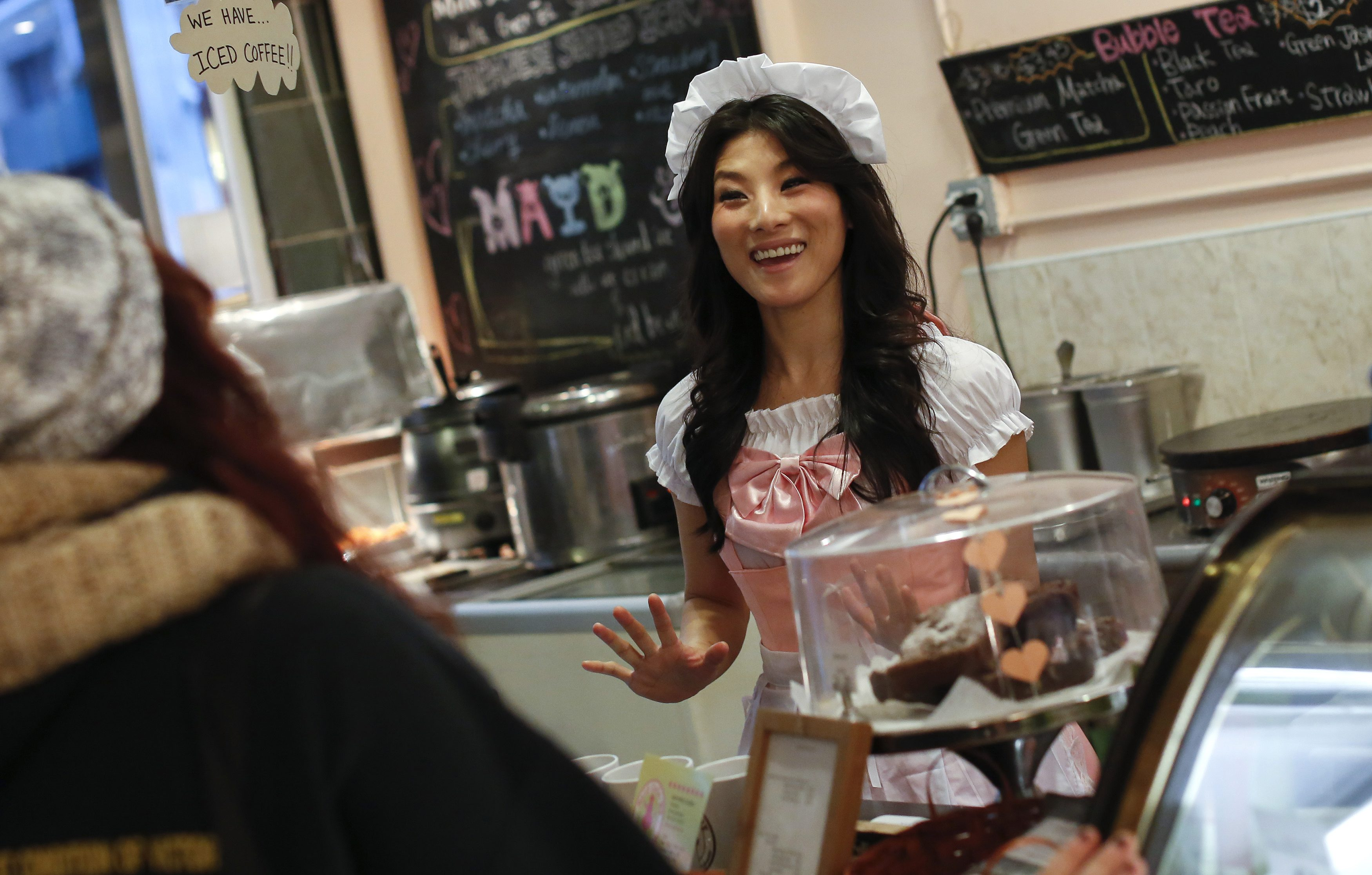 Reni Mimura, a waitress at the Maid Cafe New York, speaks with customers in New York November 20, 2013.