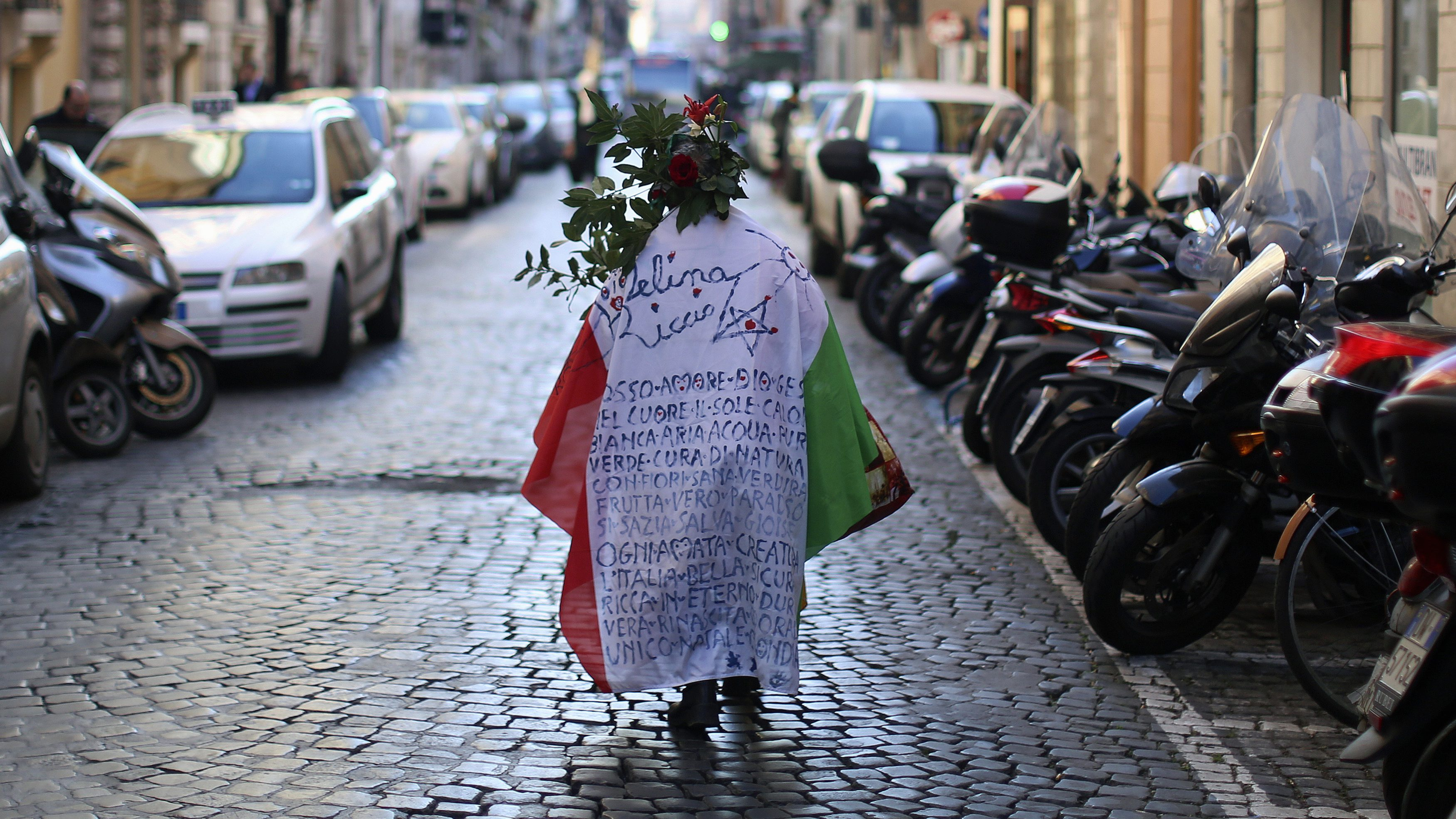 """A woman walks while wearing an Italian national flag before a demonstration organised by """"People from the Pitchfork Movement"""" to protest against economic insecurity and the government in downtown Rome December 18, 2013. The """"pitchfork"""" movement  was originally a loosely organised group of farmers from Sicily. REUTERS/Alessandro Bianchi (ITALY - Tags: BUSINESS CIVIL UNREST POLITICS EMPLOYMENT) - RTX16N7S"""