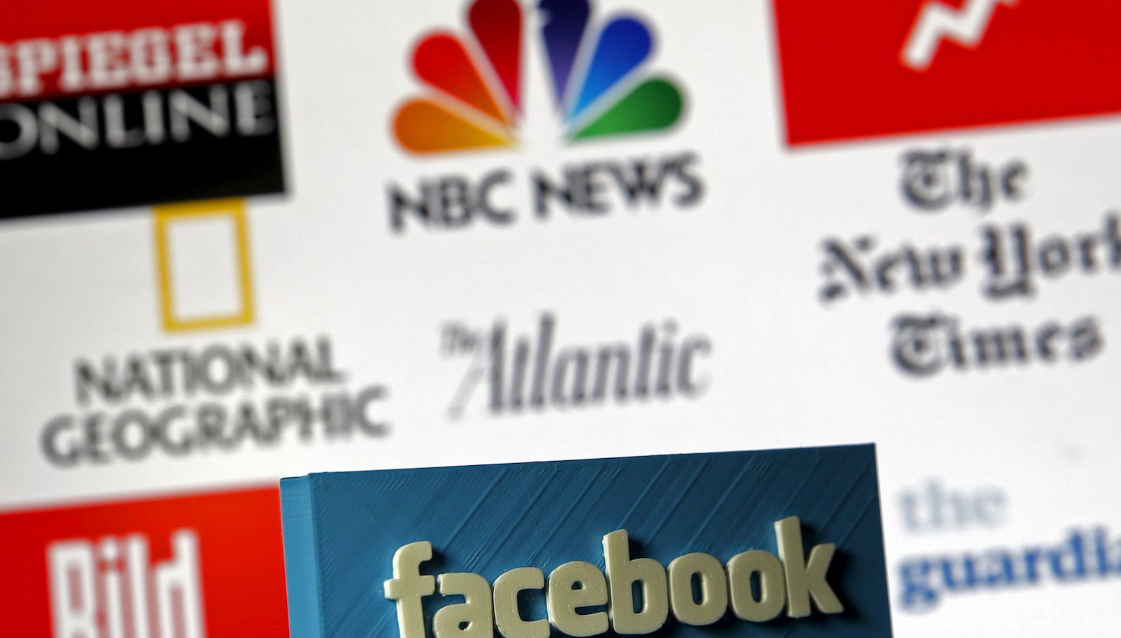 """A 3D-printed Facebook logo is seen in front of logos of news publishers it has tied up with, in this picture illustration made in Zenica, Bosnia and Herzegovina on May 15, 2015. Facebook Inc tied up with nine news publishers to launch """"Instant Articles"""" that will let them publish articles directly to the social network's mobile news feeds. Instant Articles will let stories load more than 10 times faster than standard mobile web articles and will include content from publishers such as the New York Times, BuzzFeed and National Geographic, Facebook said in a blog post on its website. The other launch partners for Instant Articles are NBC, The Atlantic, The Guardian, BBC News, Spiegel and Bild, Facebook said.    REUTERS/Dado Ruvic - RTX1D3H3"""