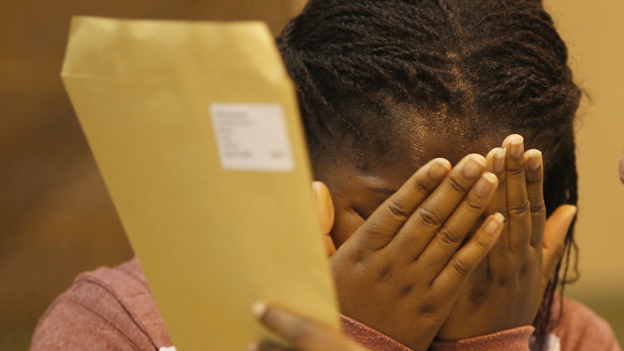 A student reacts as she stands with a teacher after receiving her A-level exam results at the Harris...