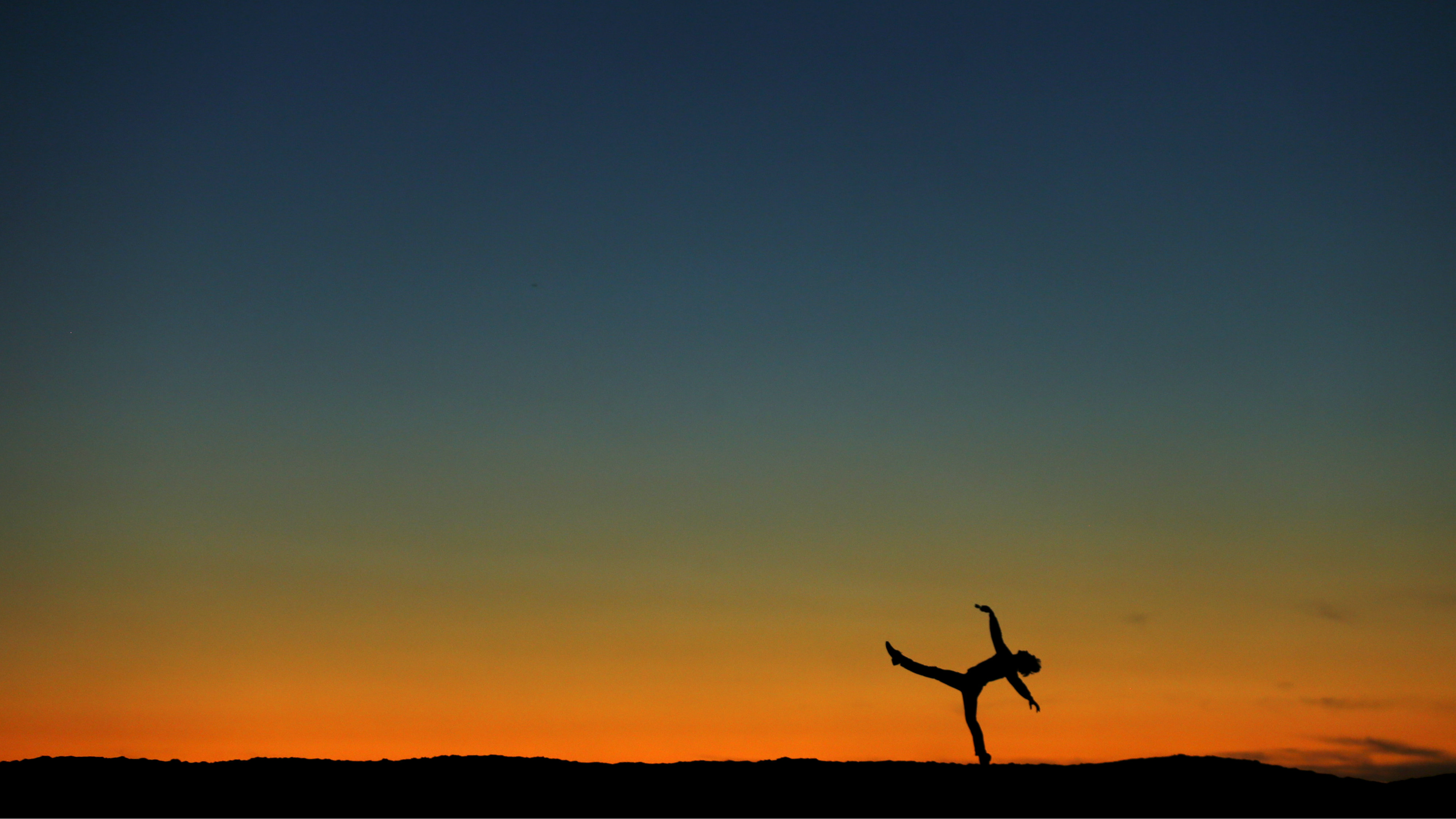 :Former ballerina Luke Willis plays on a sand berm after sunset in Encinitas