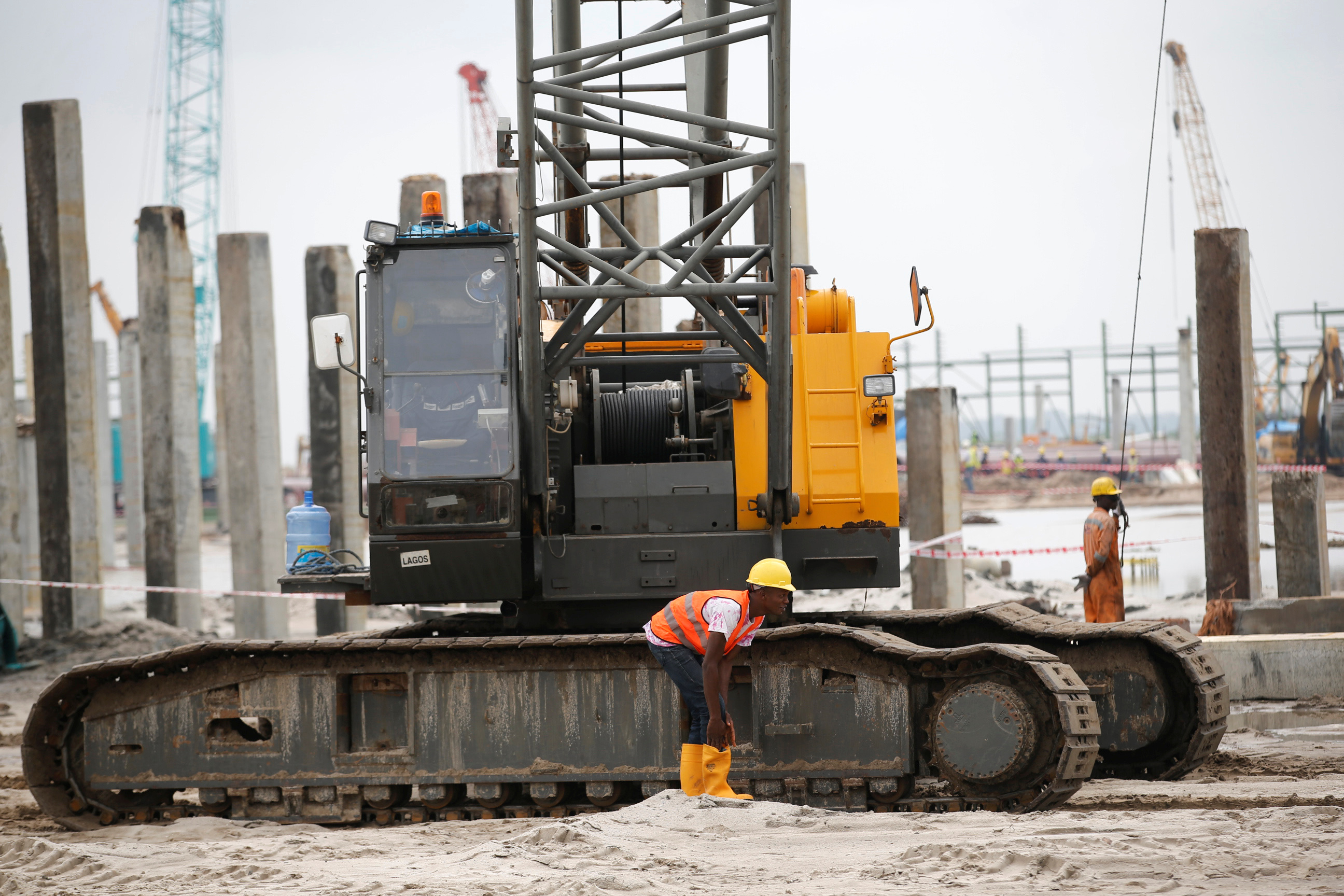 A construction worker is seen near a machine on a site during a facility tour at the proposed Dangote oil refinery site near Akodo beach in the outskirt of Nigeria's commercial capital Lagos June 25, 2016. REUTERS/Akintunde Akinleye - RTX2I77I