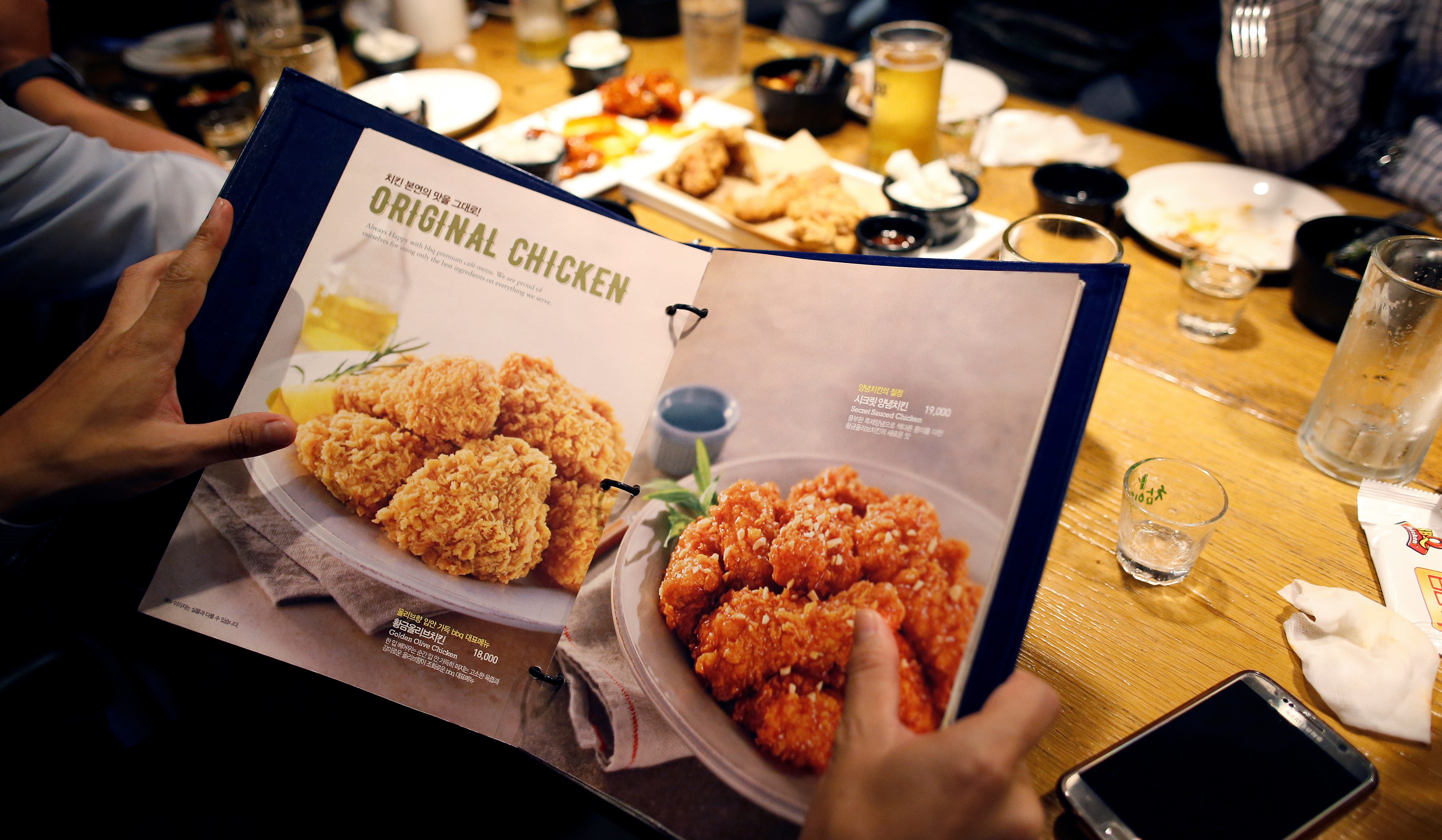 A man looks at a menu for fried chicken at a pub in Seoul, South Korea, October 11, 2016.
