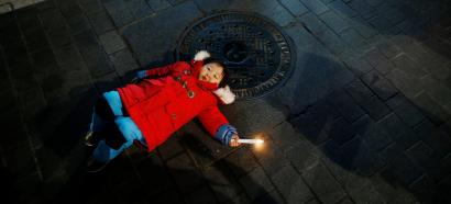 A girl holding a candle lies on a street during a protest demanding South Korean President Park Geun-hye's resignation in Seoul, South Korea, January 7, 2017.