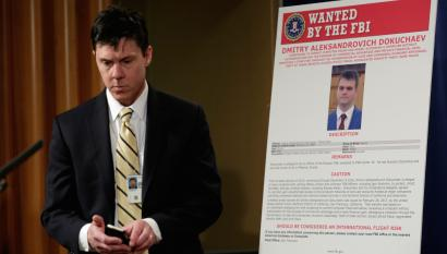 A Department of Justice staffer walks past a poster of a suspected Russian hacker
