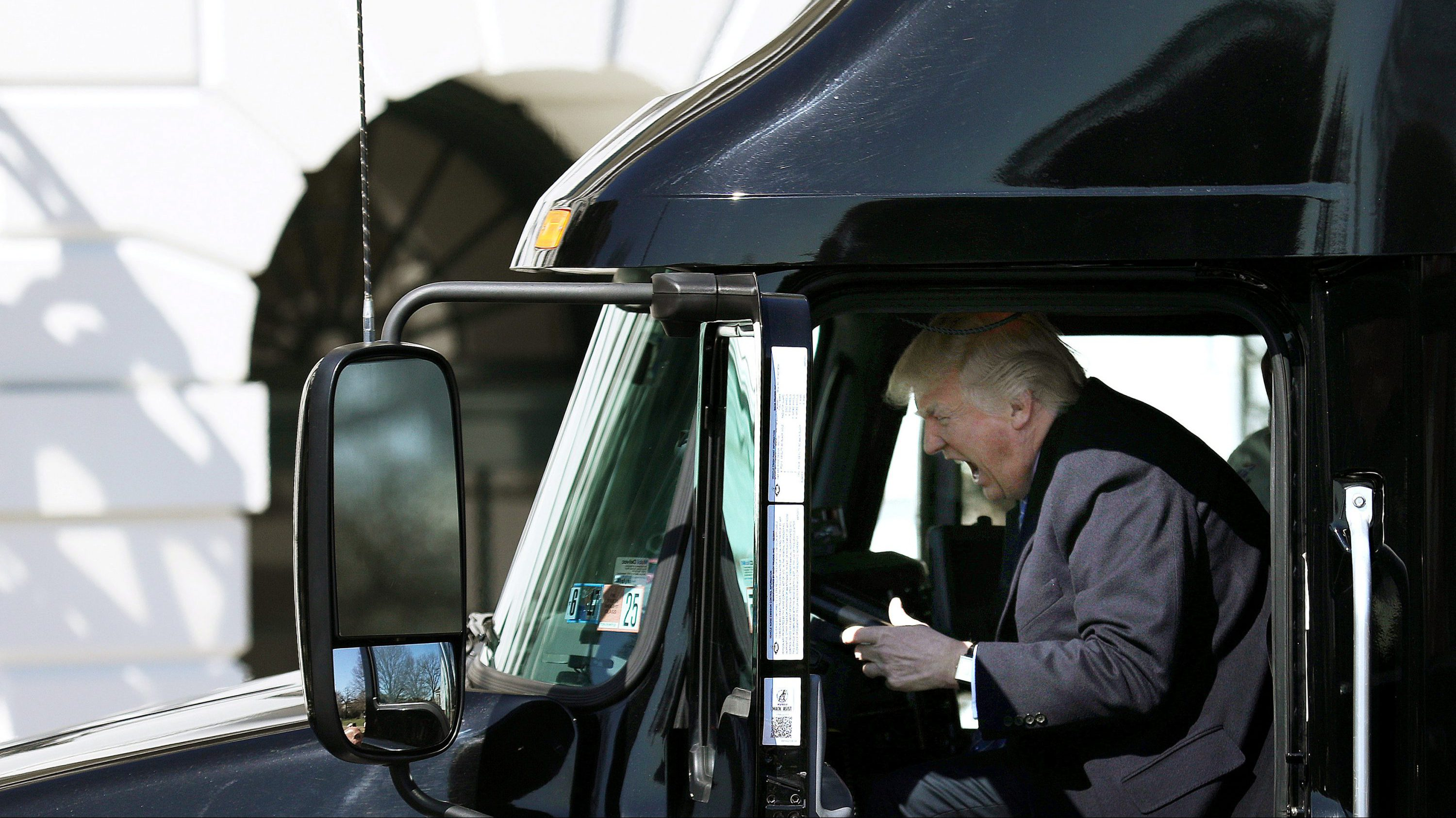 U.S. President Donald Trump reacts as he sits on a truck while he welcomes  truckers and CEOs to attend a meeting regarding healthcare at the White House in Washington, U.S., March 23, 2017.